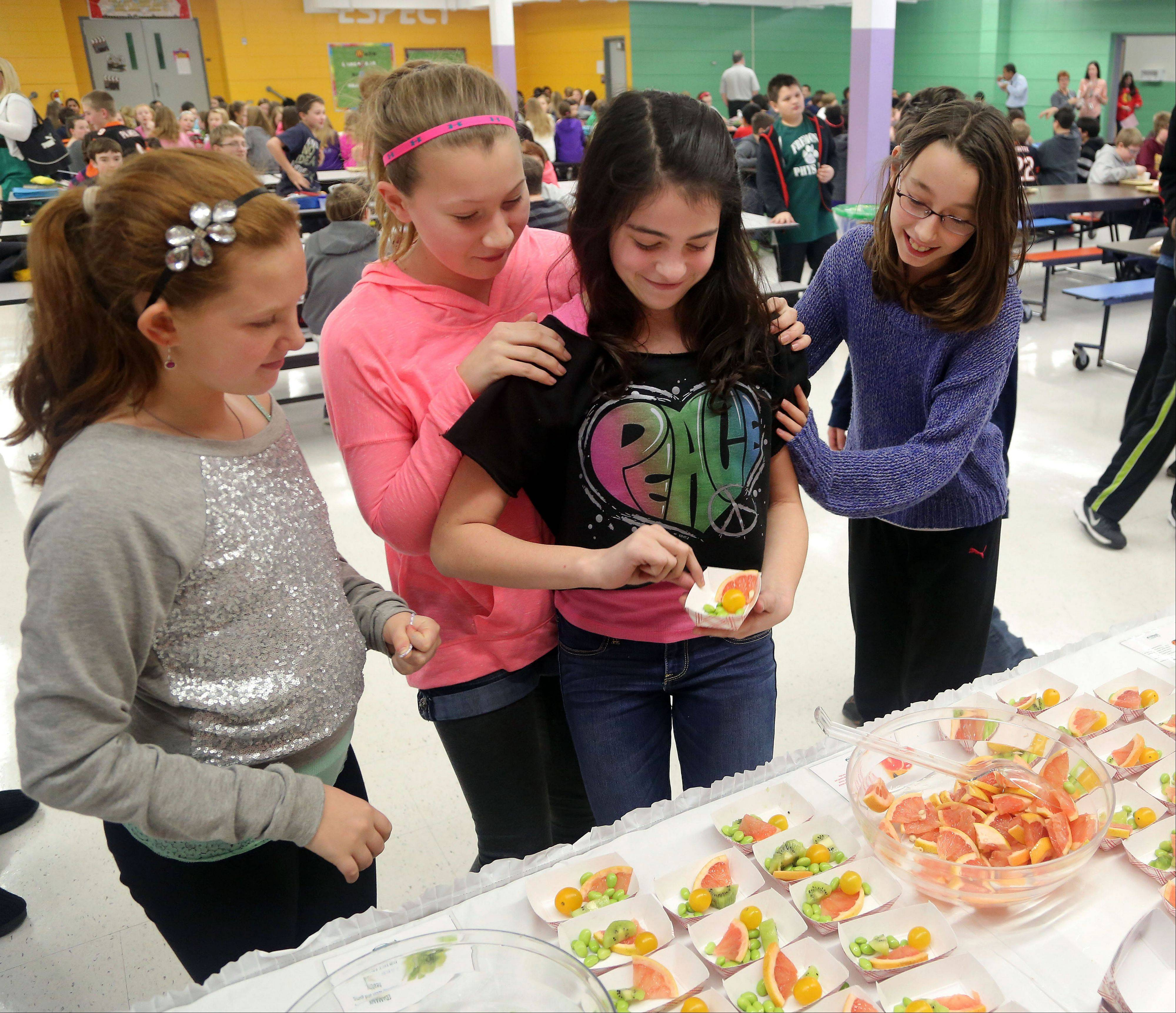 Sixth graders, from left, Mia Bulmash, Alexis Naddy, Lilly Port and Alexandra Merkel, test out new fruits and vegetables Thursday that will be introduced to their hot lunch menu at a Fremont Middle School in Mundelein.