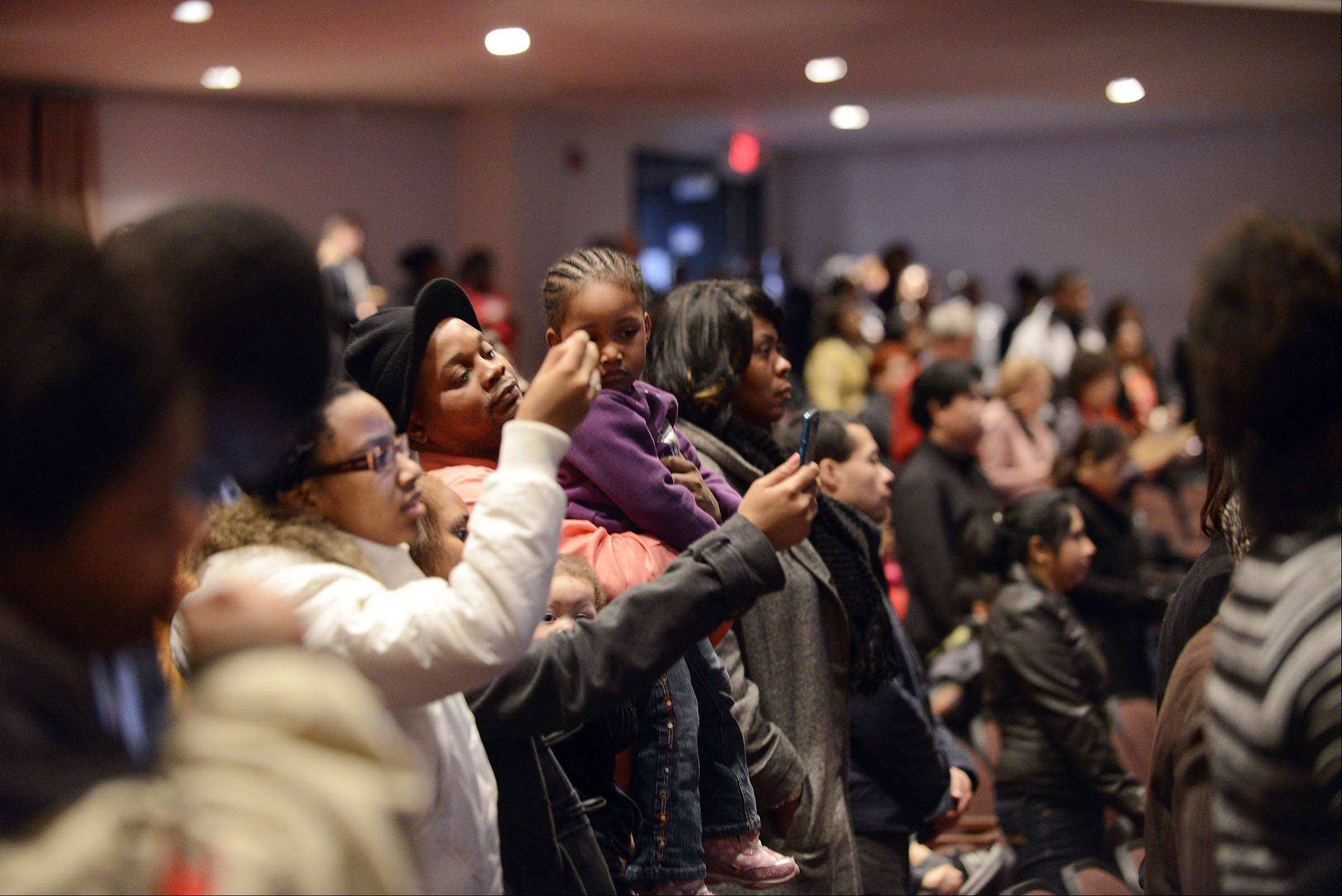 Audience members watch and record the 29th Annual Dr. Martin Luther King Jr. Program at the Hemmens Auditorium in Elgin on Sunday. The event celebrated King's legacy through words, song, prayer and dance.