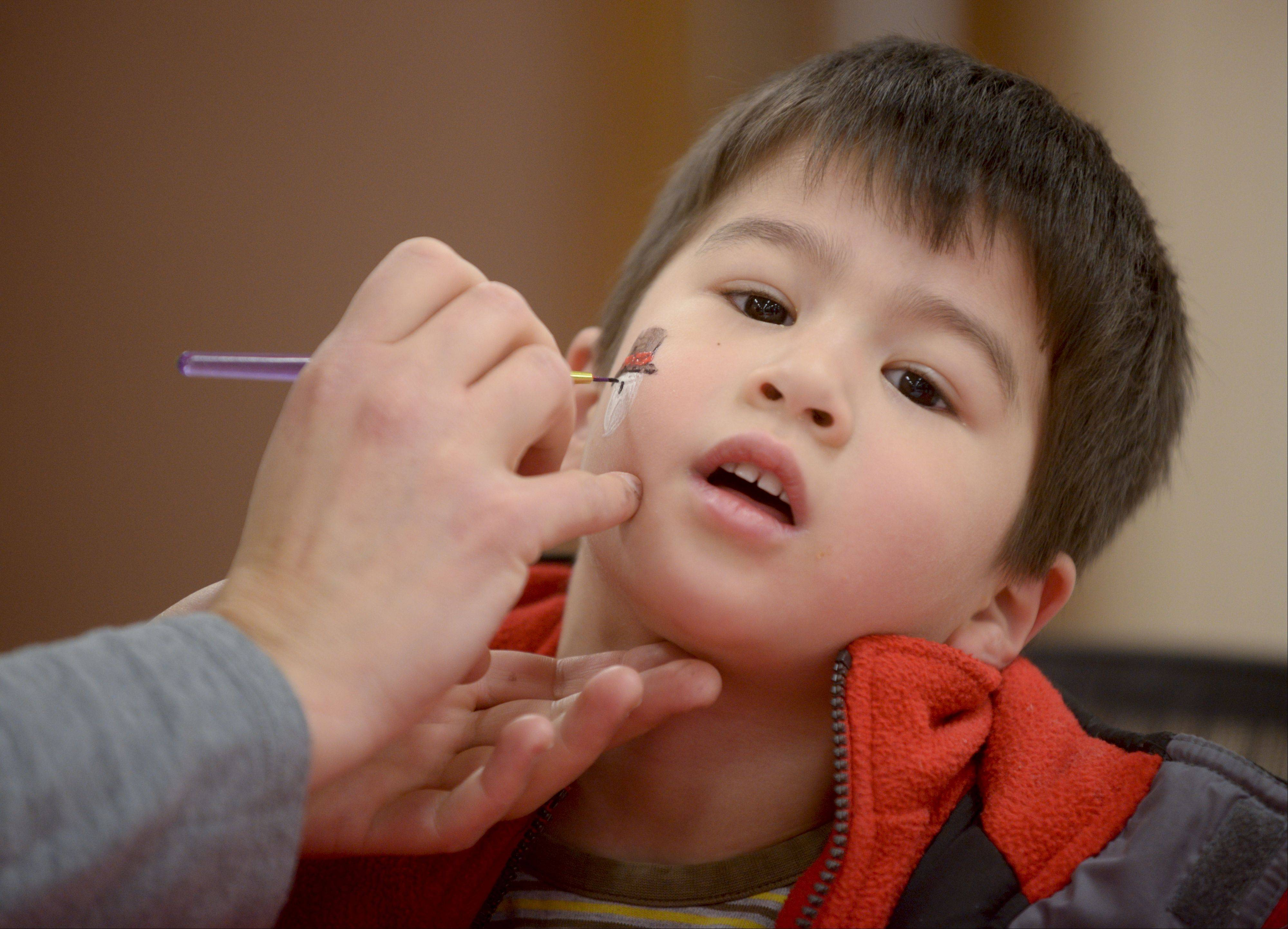 Jake Gizel, 3, of Streamwood gets a snowman painted on his face by Anna Pecoraro during the at Addison's annual WinterFEST at Community Park. The event Sunday featured winter-themed events like snow golf and marshmallow roasting, as well as indoor activities like an obstacle course and bounce house.