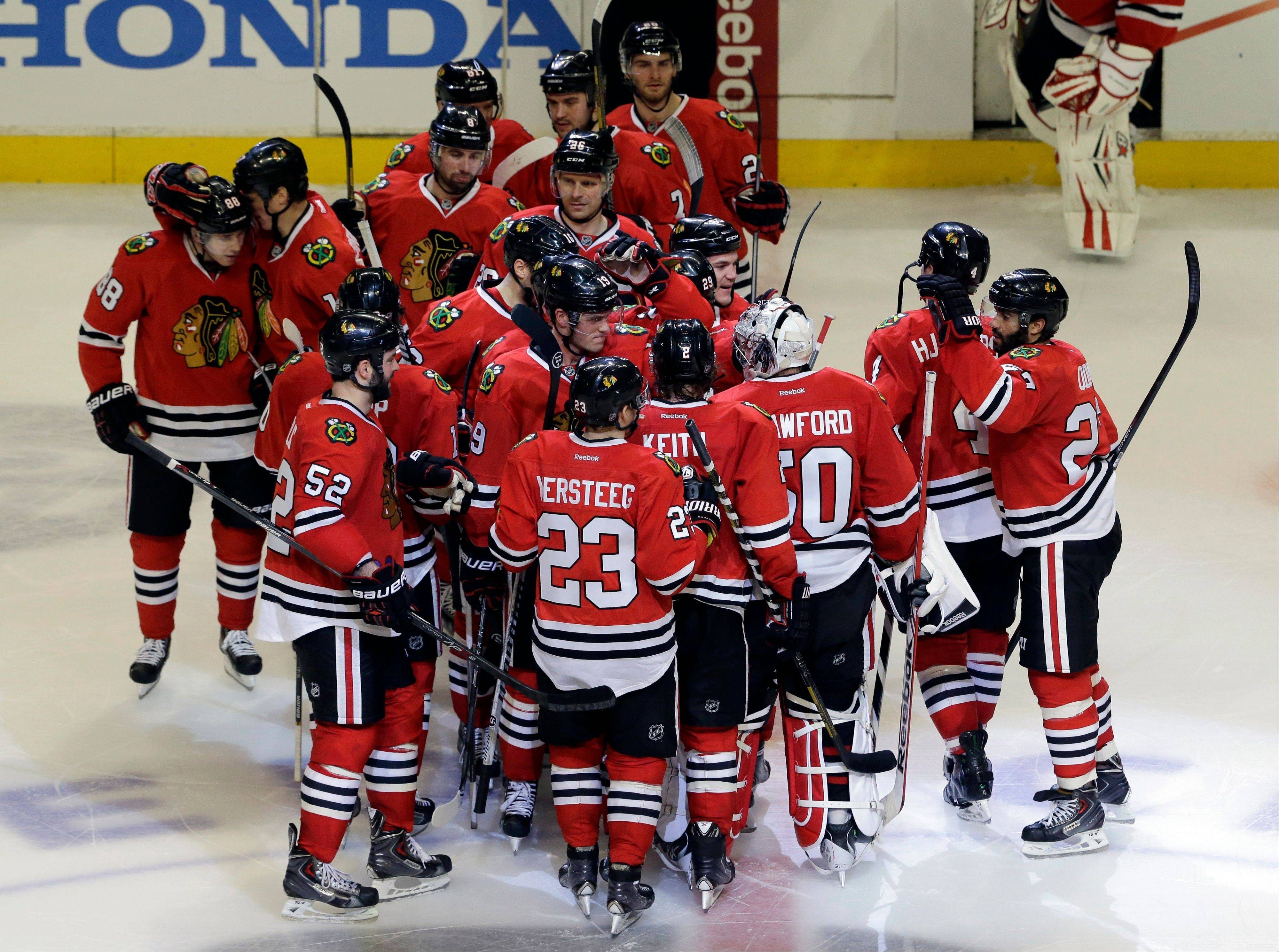Blackhawks goalie Corey Crawford (50) celebrates with teammates after the Blackhawks defeated the Boston Bruins 3-2 following their shootout period of an NHL hockey game in Chicago, Sunday, Jan. 19, 2014.