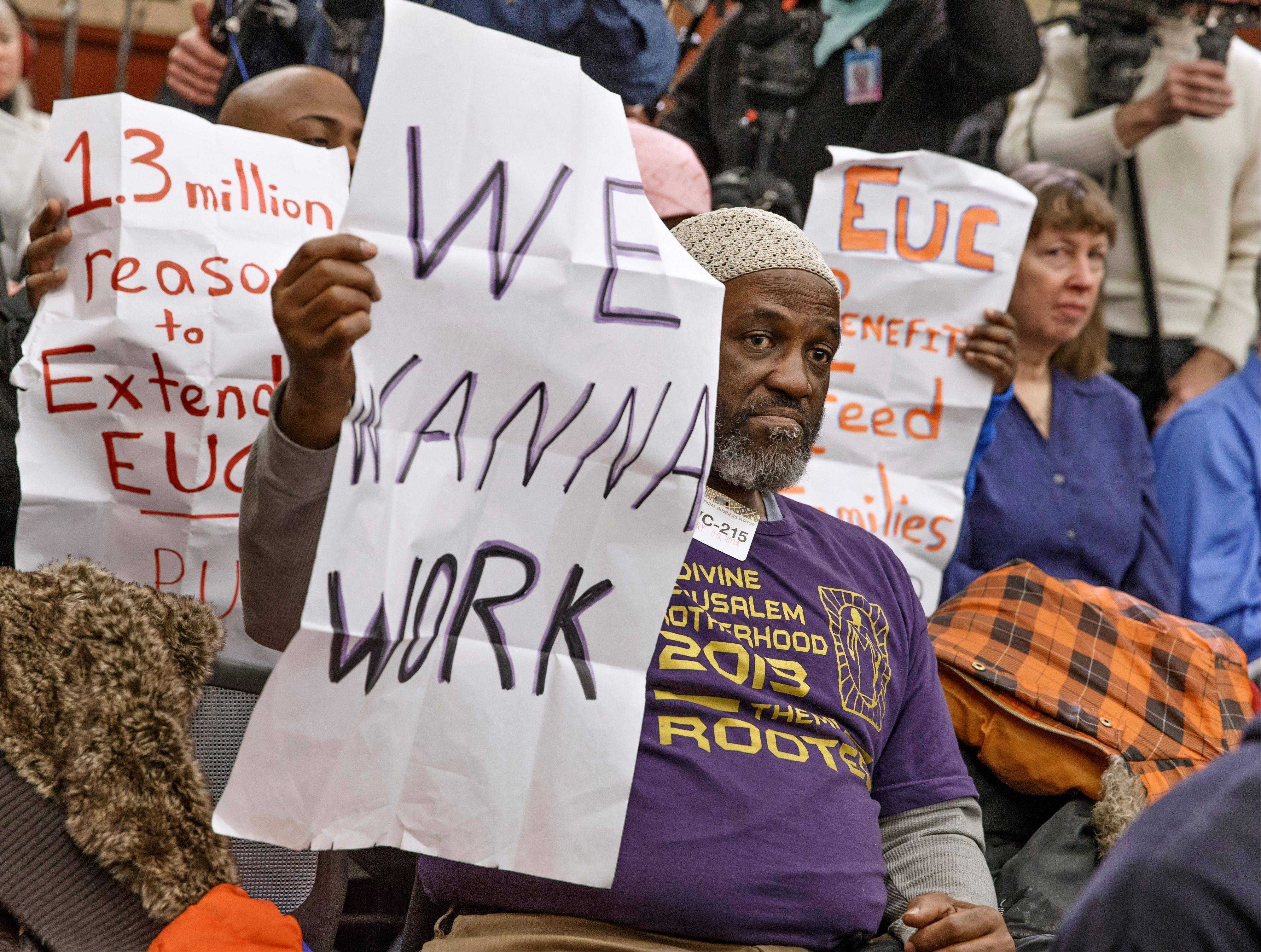 Audience members hold signs appealing for jobs as they attend a Democratic news conference about extending unemployment insurance benefits which expired Dec. 28, on Capitol Hill in Washington. Unemployment in America has gone down in the last several years, but it remains a serious drag on the economy.
