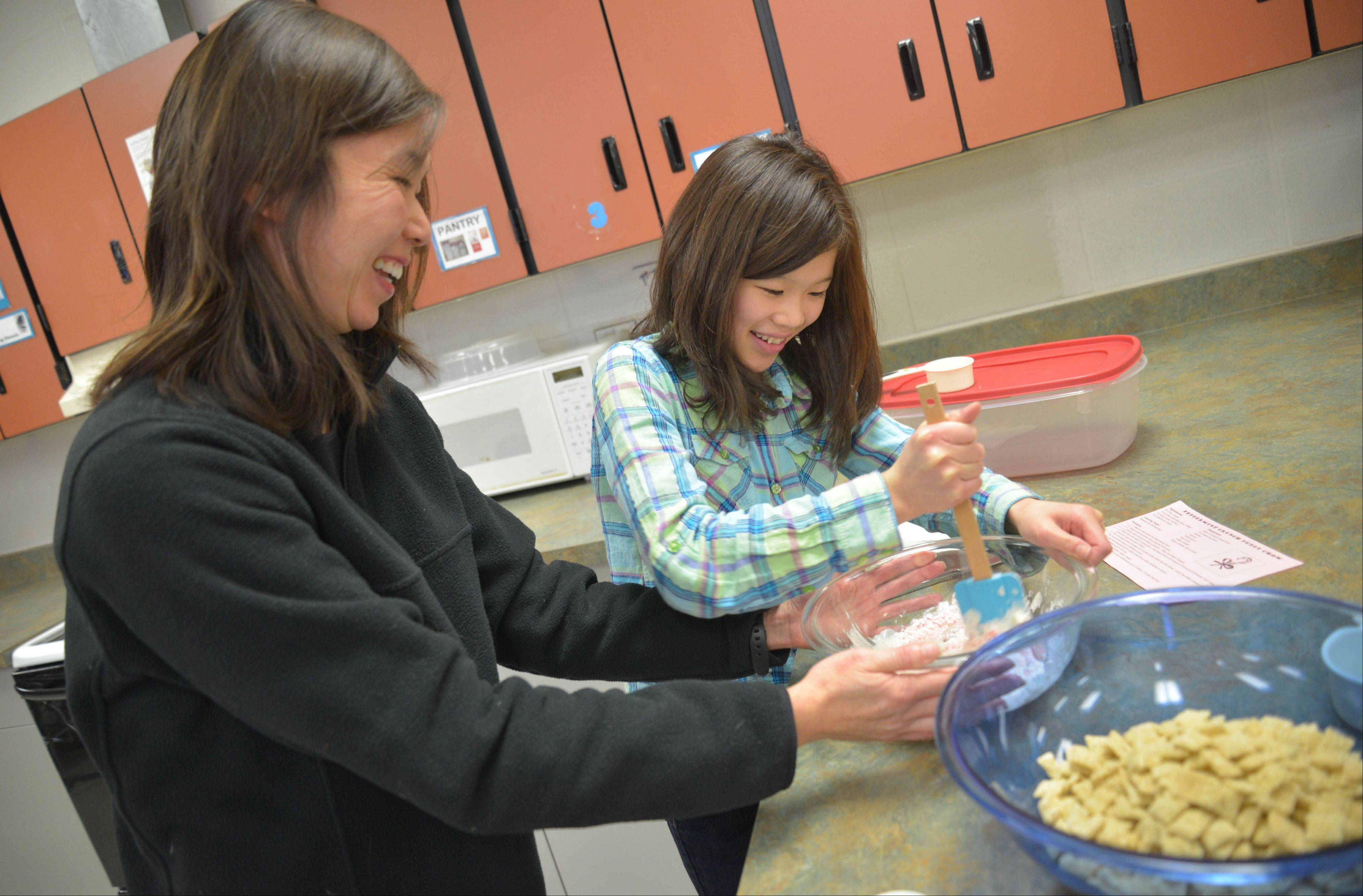 Frances Hung of Naperville and her daughter Elizabeth, 11, mix ingredients for peppermint crunch puppy chow during Toasty Tales, Gregory Middle School�s first family reading night. The cooking activity challenged kids to use their reading skills to follow a recipe, said Esther Bevan, director of the school�s library media center.