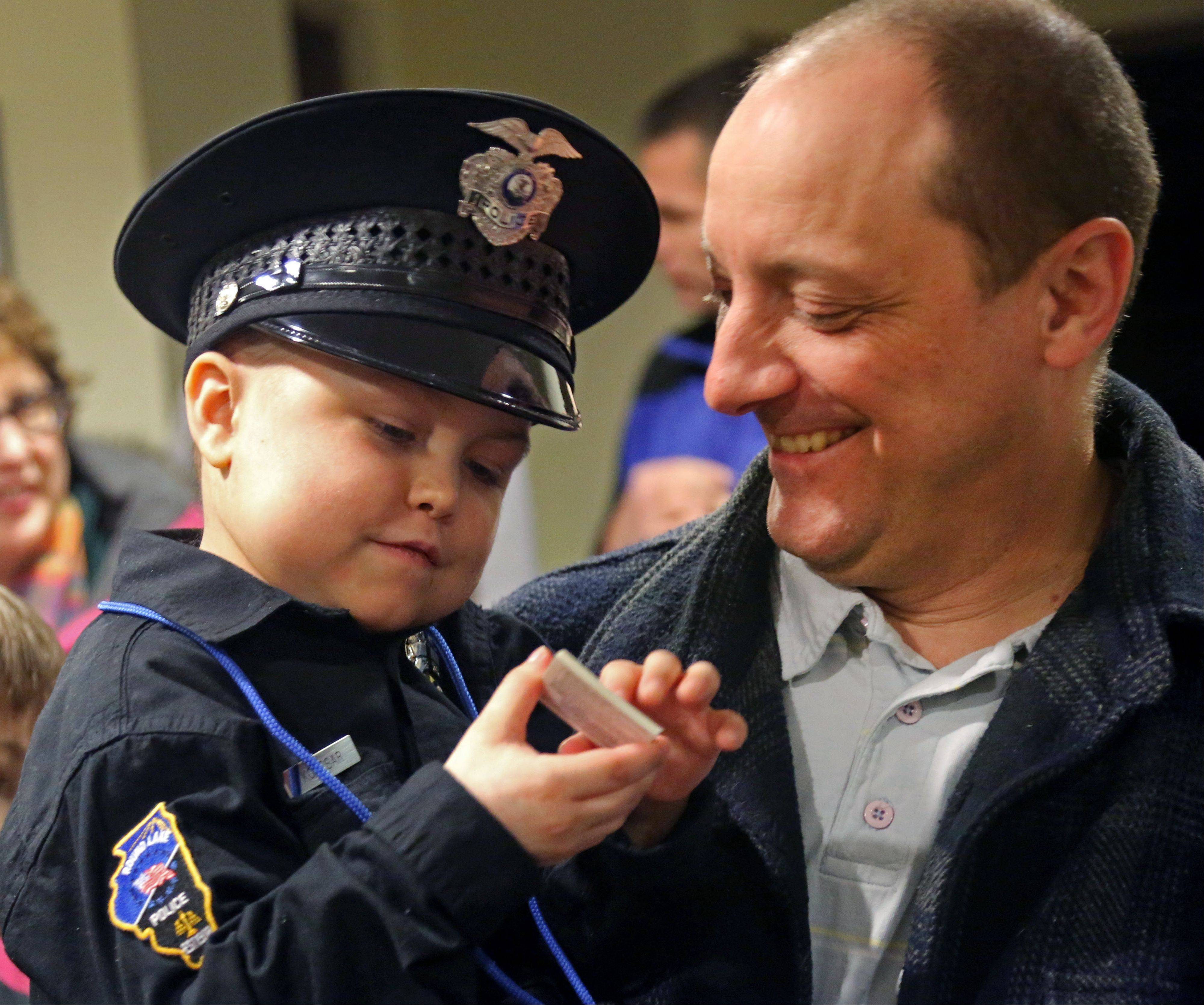 Six-year-old Jonah Kolesar of Round Lake is held by his father, Mitchell, after being sworn in Monday night as a junior reserve police officer during a ceremony at the Round Lake village board meeting. Jonah suffers from an autoimmune disease called IPEX Syndrome.