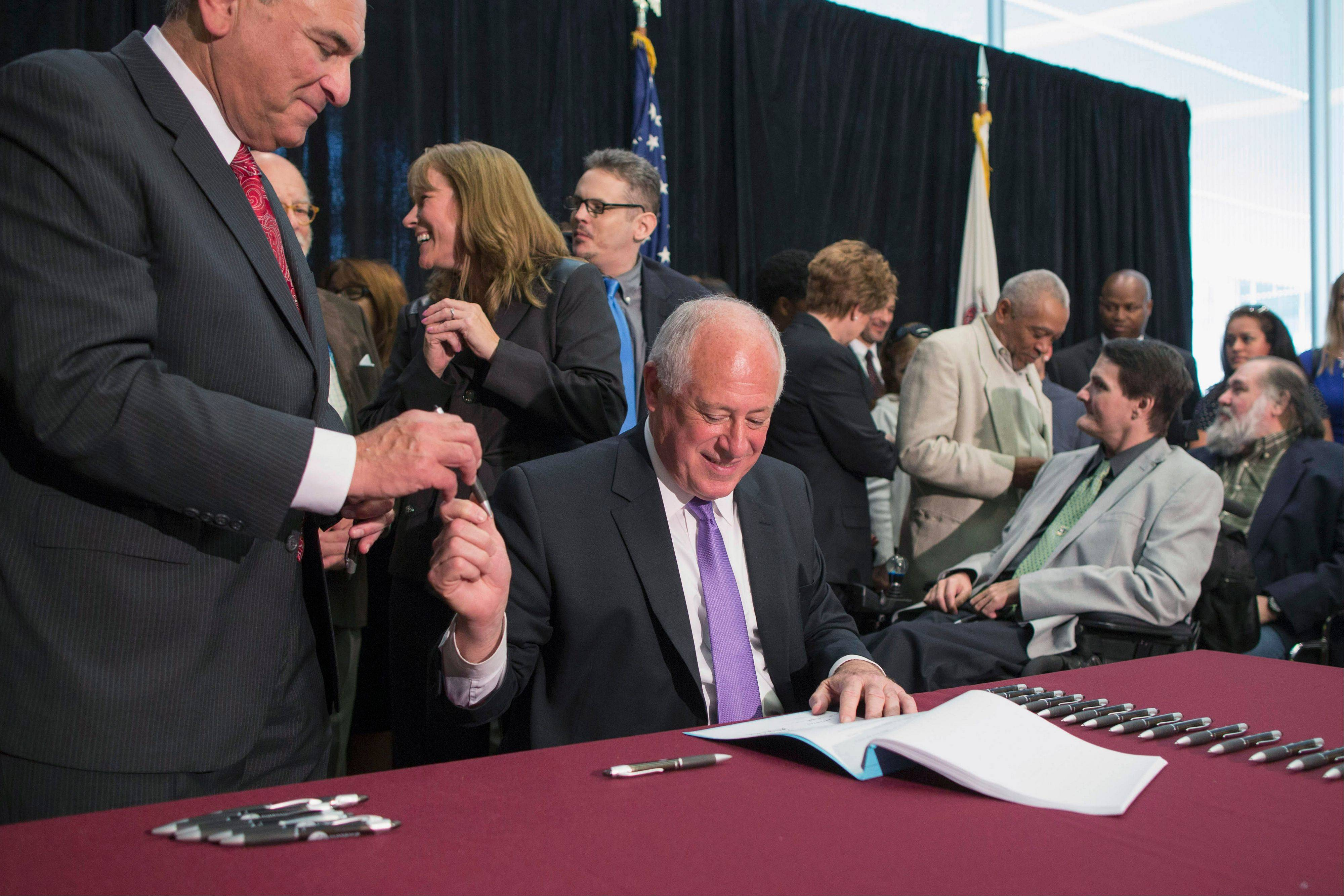Gov. Pat Quinn hands a pen to state Rep. Lou Lang as he signs a bill legalizing medical marijuana in August.