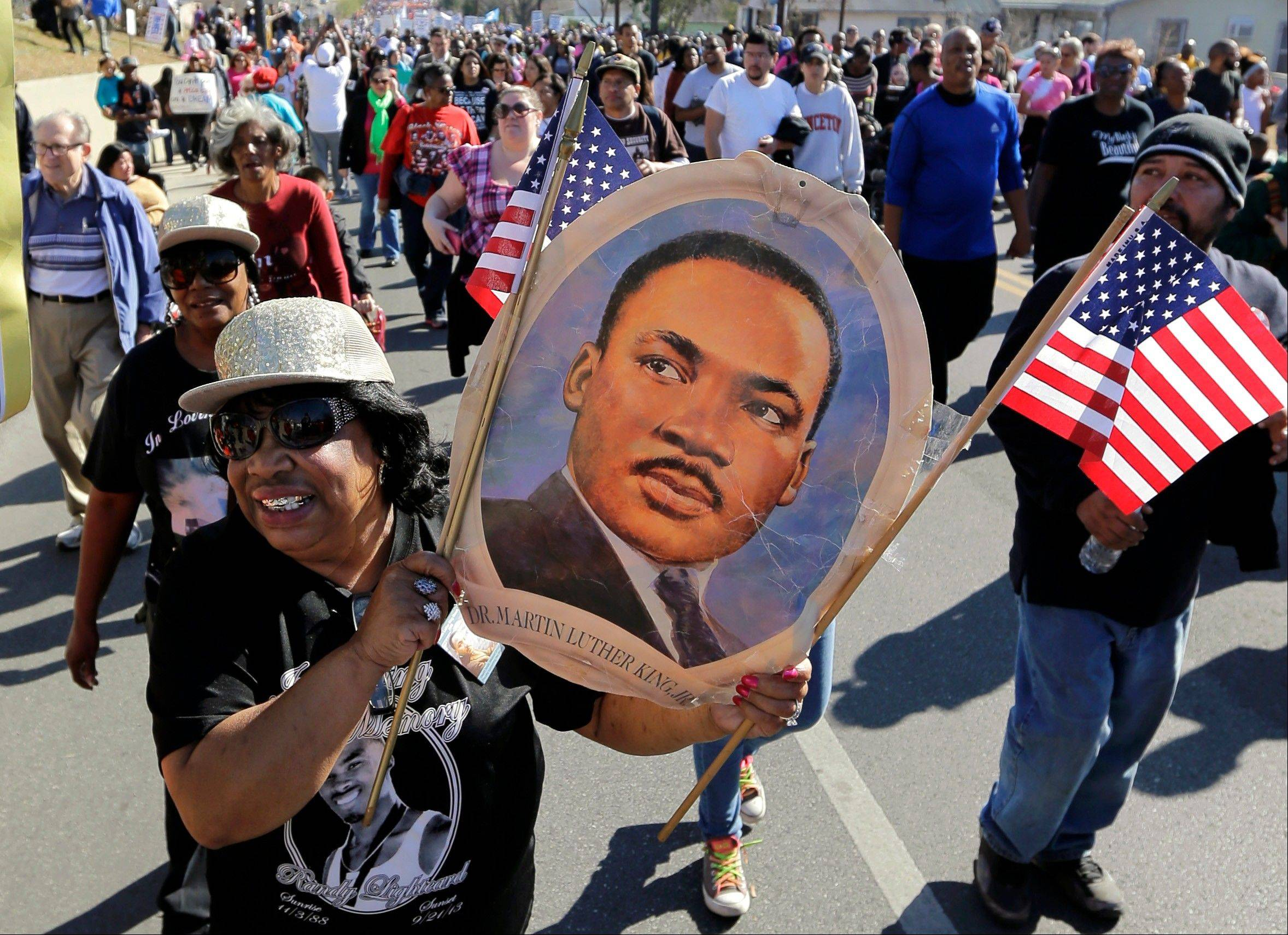 Robbie Thompson participates in a march honoring Martin Luther King Jr., Monday, Jan. 20, 2014, in San Antonio. Parades and celebrations have been scheduled across Texas to honor Martin Luther King Jr. on the federal holiday in his name.