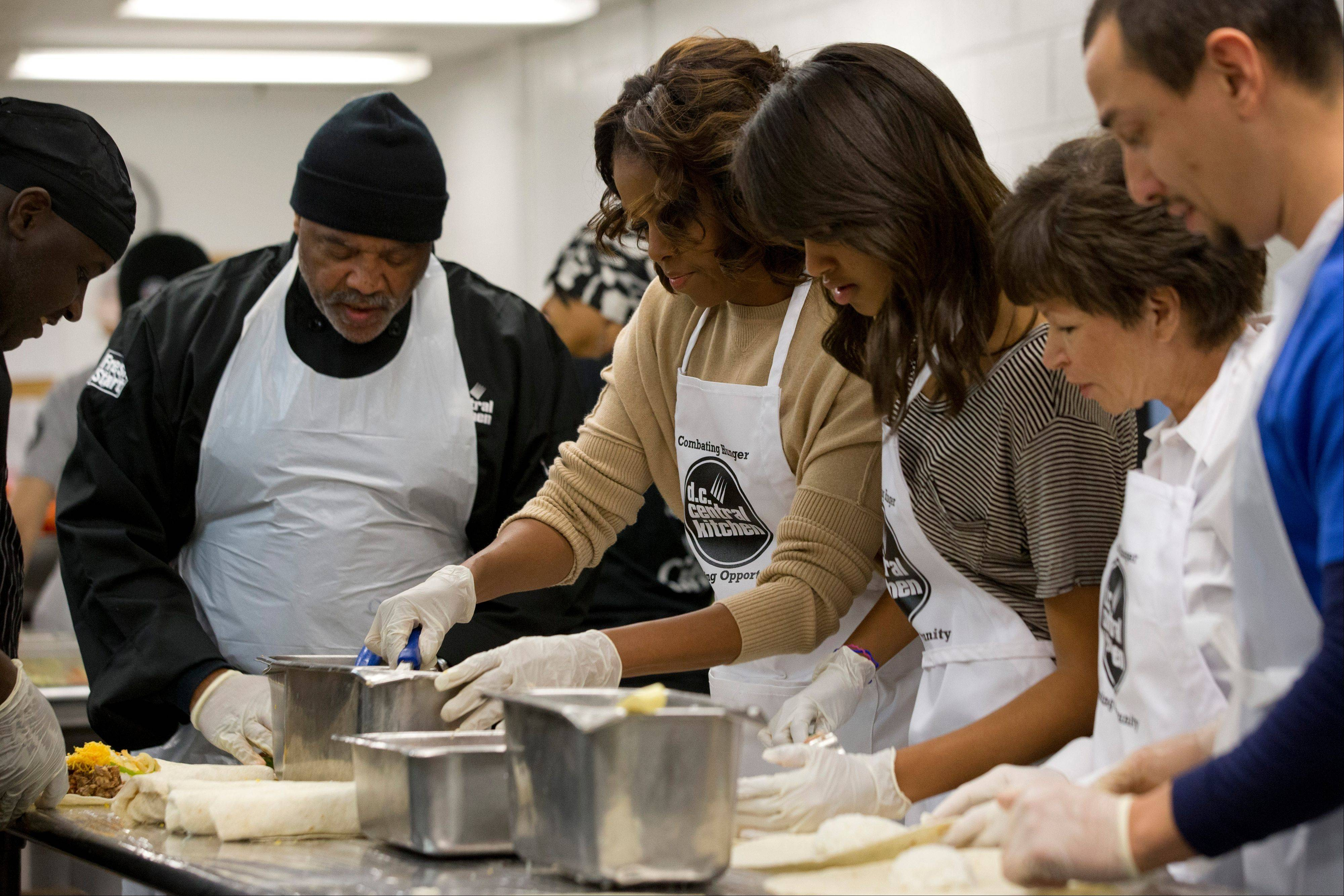 First lady Michelle Obama, center, with daughter Malia Obama and presidential adviser Valerie Jarrett, make burritos at DC Central Kitchen as part of a service project in honor of Martin Luther King, Jr. Day on Monday in Washington. Also helping were President Barack Obama and daughter Sasha Obama.