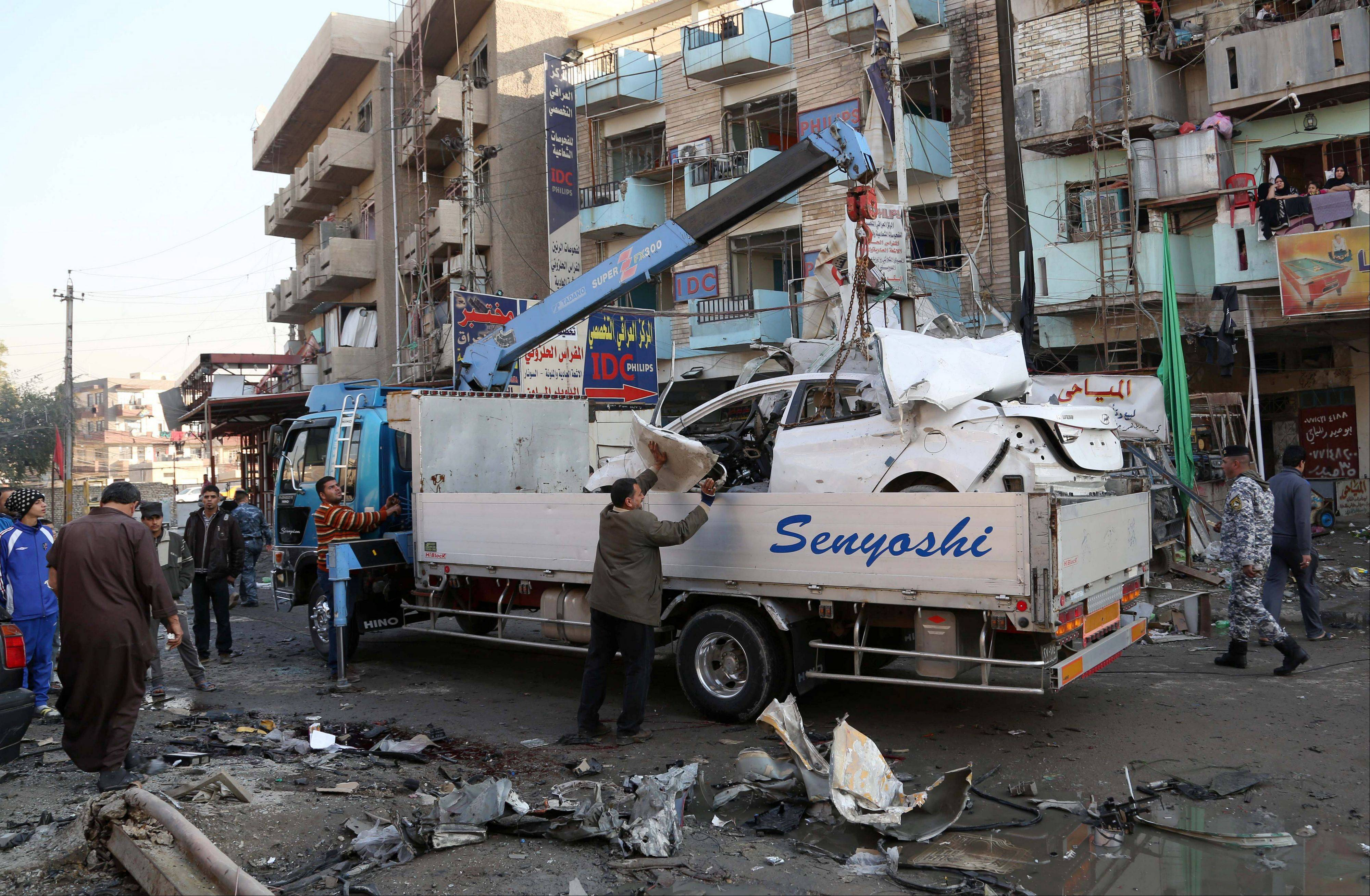 Municipality workers remove debris while civilians inspect the site of a car bomb attack at an outdoor market in Baghdad al-Jadidah district, Iraq, Monday.