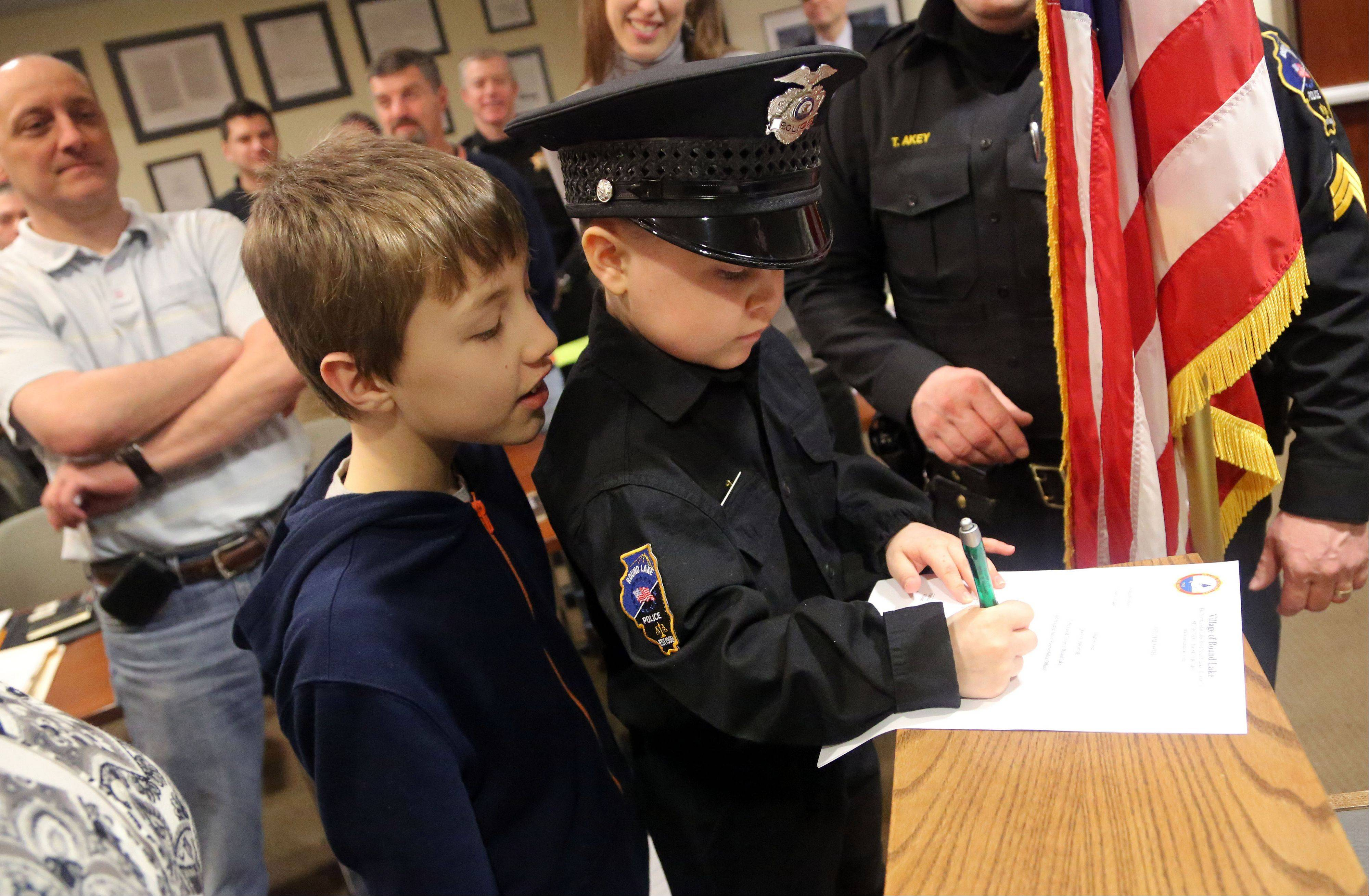 Six-year-old Jonah Kolesar, right, signs an official oath after being sworn in Monday as a junior reserve police officer as his 9-year-old brother Nicholas looks on during the Round Lake village board meeting. Jonah suffers from an autoimmune disease called IPEX Syndrome.