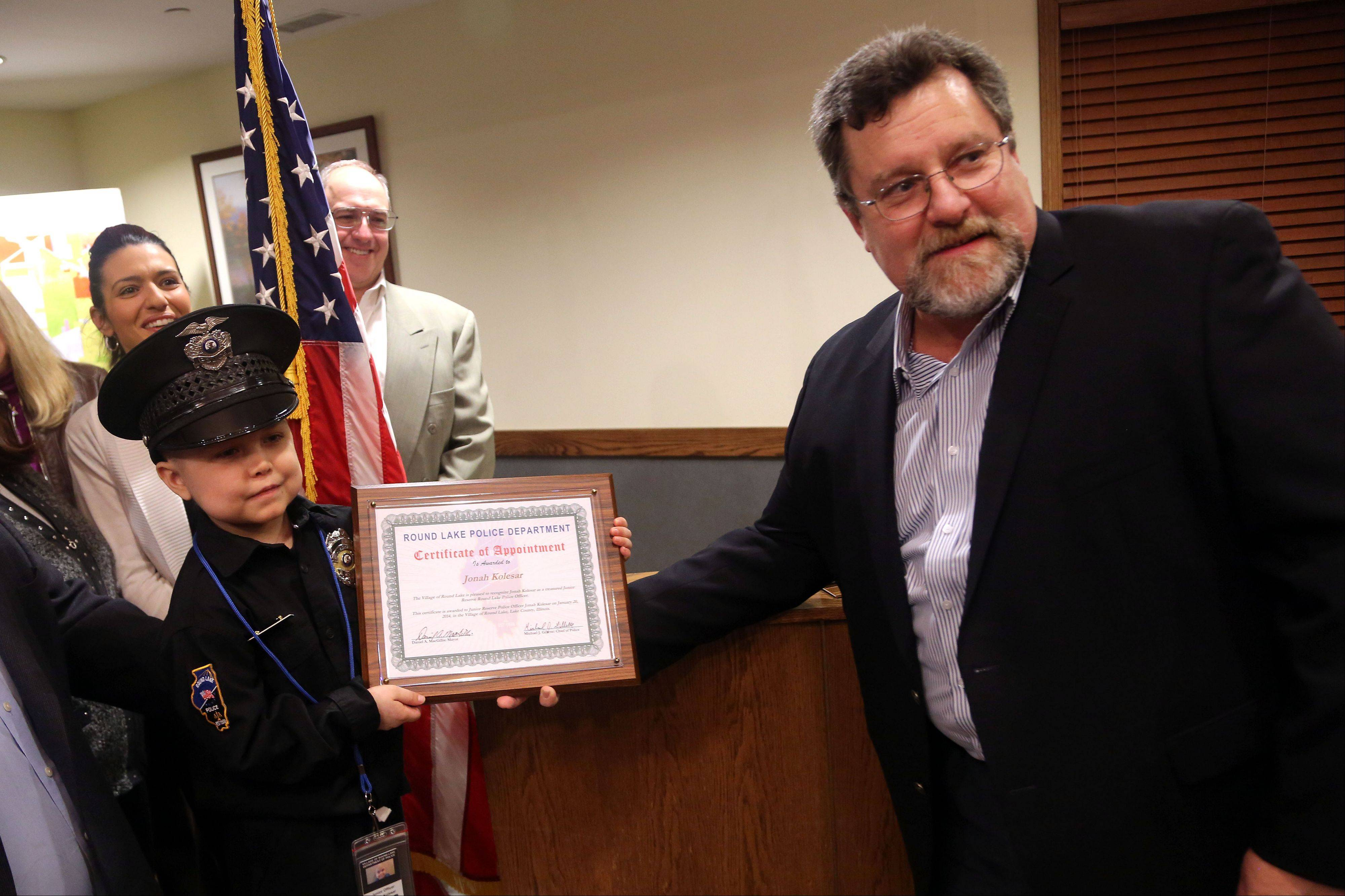 Six-year-old Jonah Kolesar of Round Lake, left, is given a certificate of appointment Monday by Round Lake Mayor Daniel MacGillis after being sworn in as a junior reserve police officer at the Round Lake village board meeting. Jonah suffers from an autoimmune disease called IPEX Syndrome.