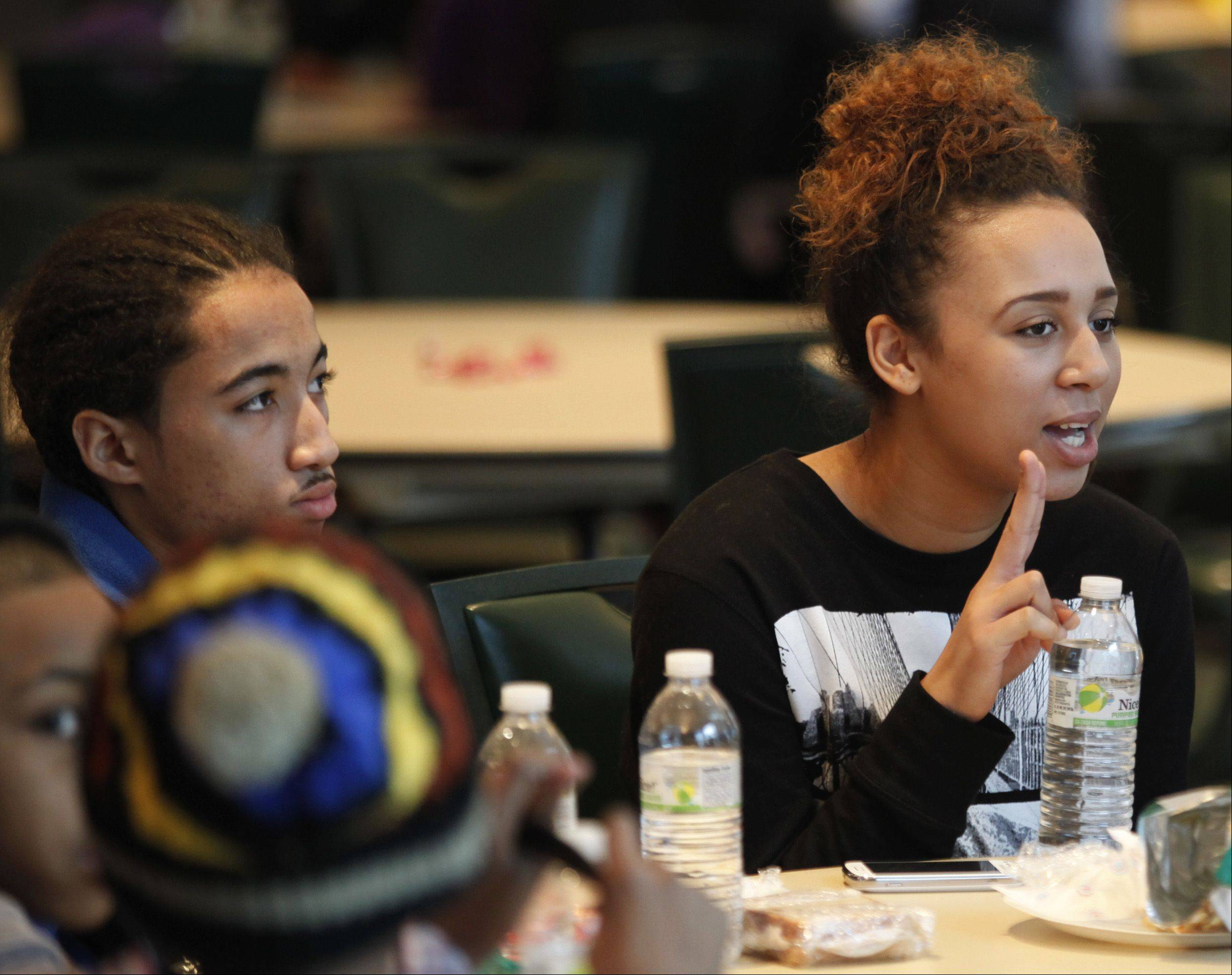 Gina Clements of Elgin, right, answers a question during a table discussion about Martin Luther King Jr. Monday with other members of the Living Gospel Youth Group including her brother Chevelle, at left. Dozens of youths from local schools, churches and other civic groups attended a luncheon in the Heritage Ballroom at The Centre of Elgin, the culmination of their volunteer work during the Day of Service event to honor the legacy of the civil rights leader.