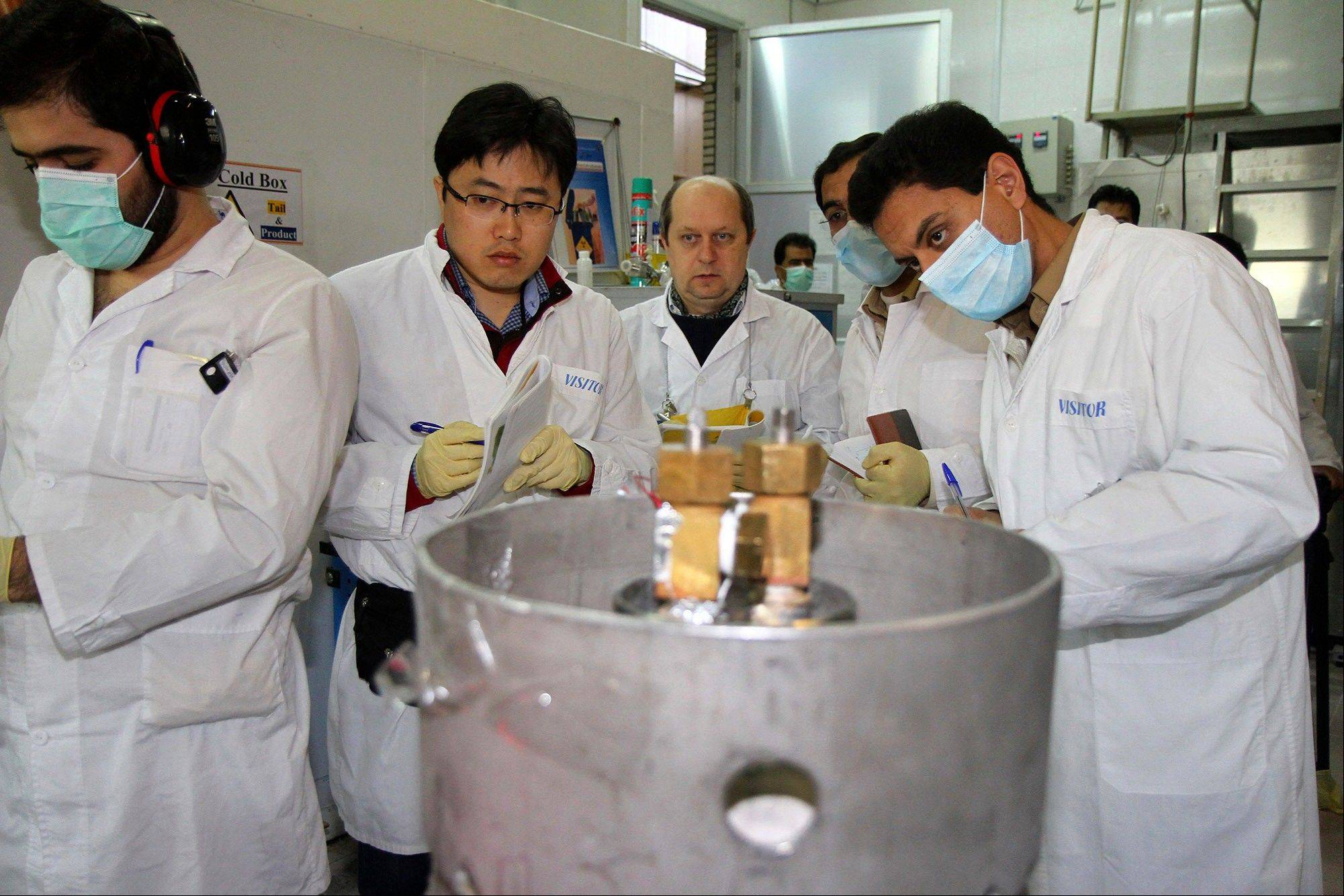 Unidentified International Atomic Energy Agency inspectors and Iranian technicians are on hand to cut the connections between the twin cascades for 20 percent uranium enrichment at Natanz facility, some 200 miles south of the capital Tehran on Monday.