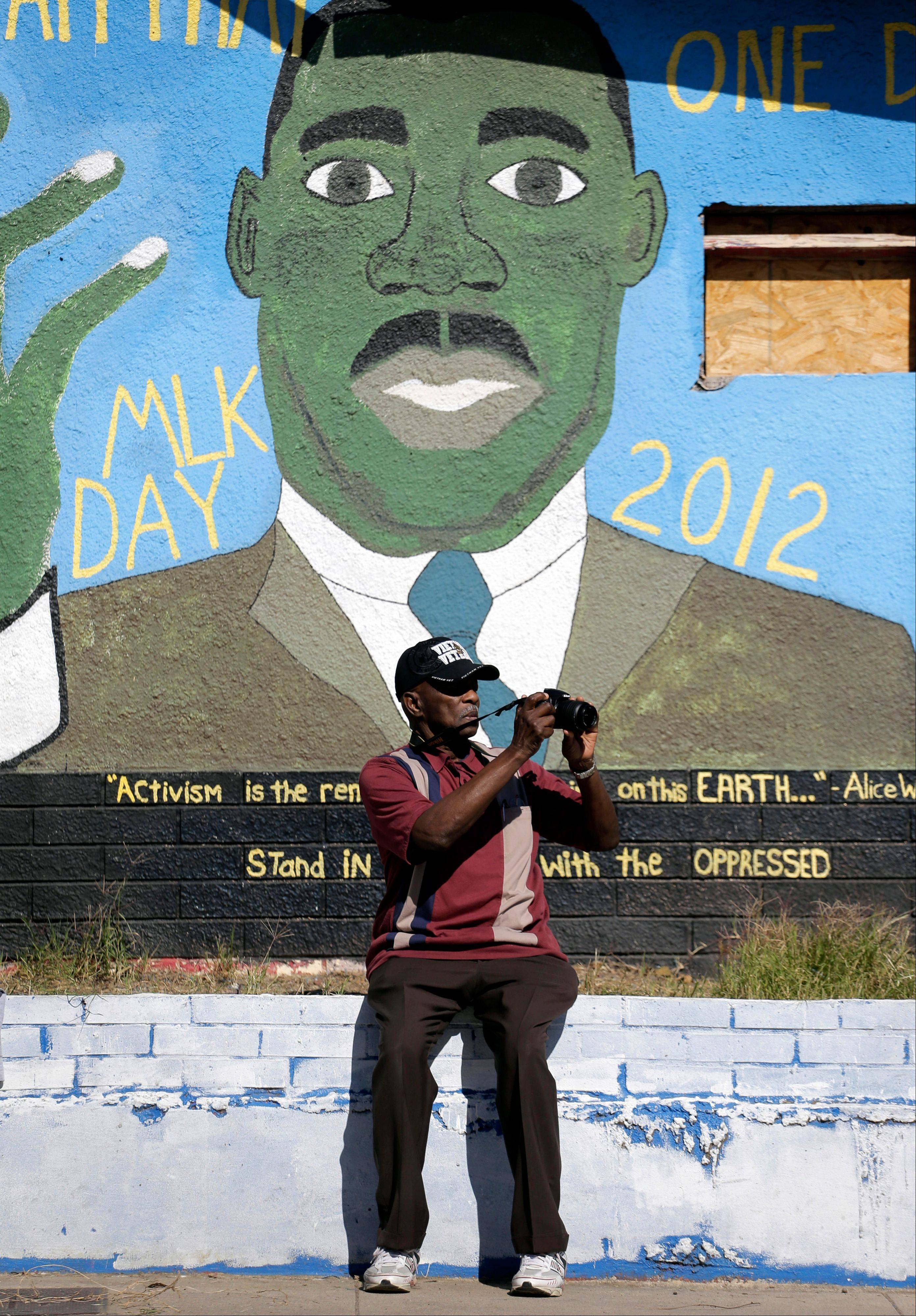 A man stops to take photos during a march honoring Martin Luther King Jr., Monday, Jan. 20, 2014, in San Antonio. Parades and celebrations have been scheduled across Texas to honor Martin Luther King Jr. on the federal holiday in his name.