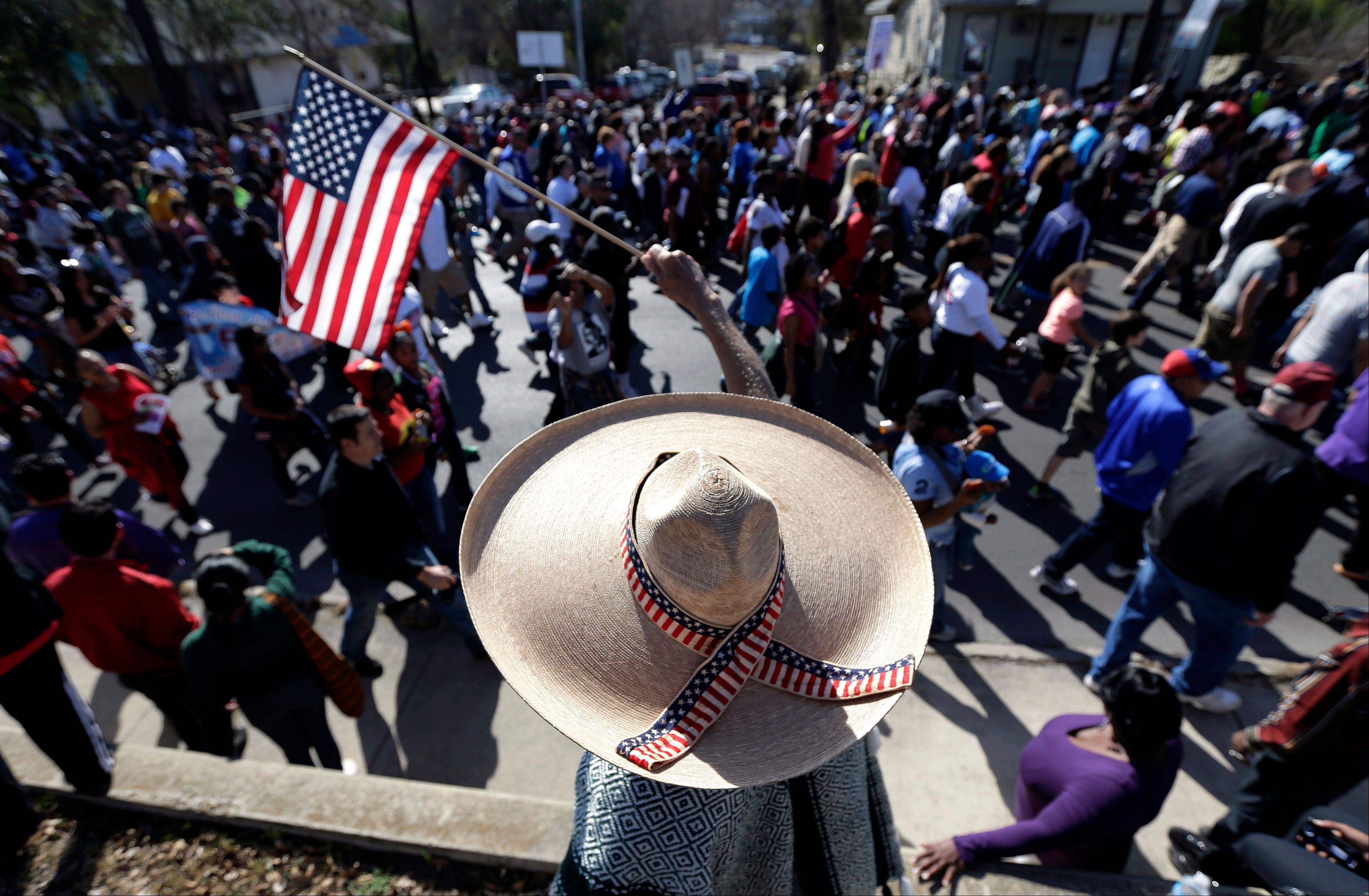 Rudy Garza waves a U.S. flag as a march honoring Martin Luther King Jr. passes, Monday, Jan. 20, 2014, in San Antonio.
