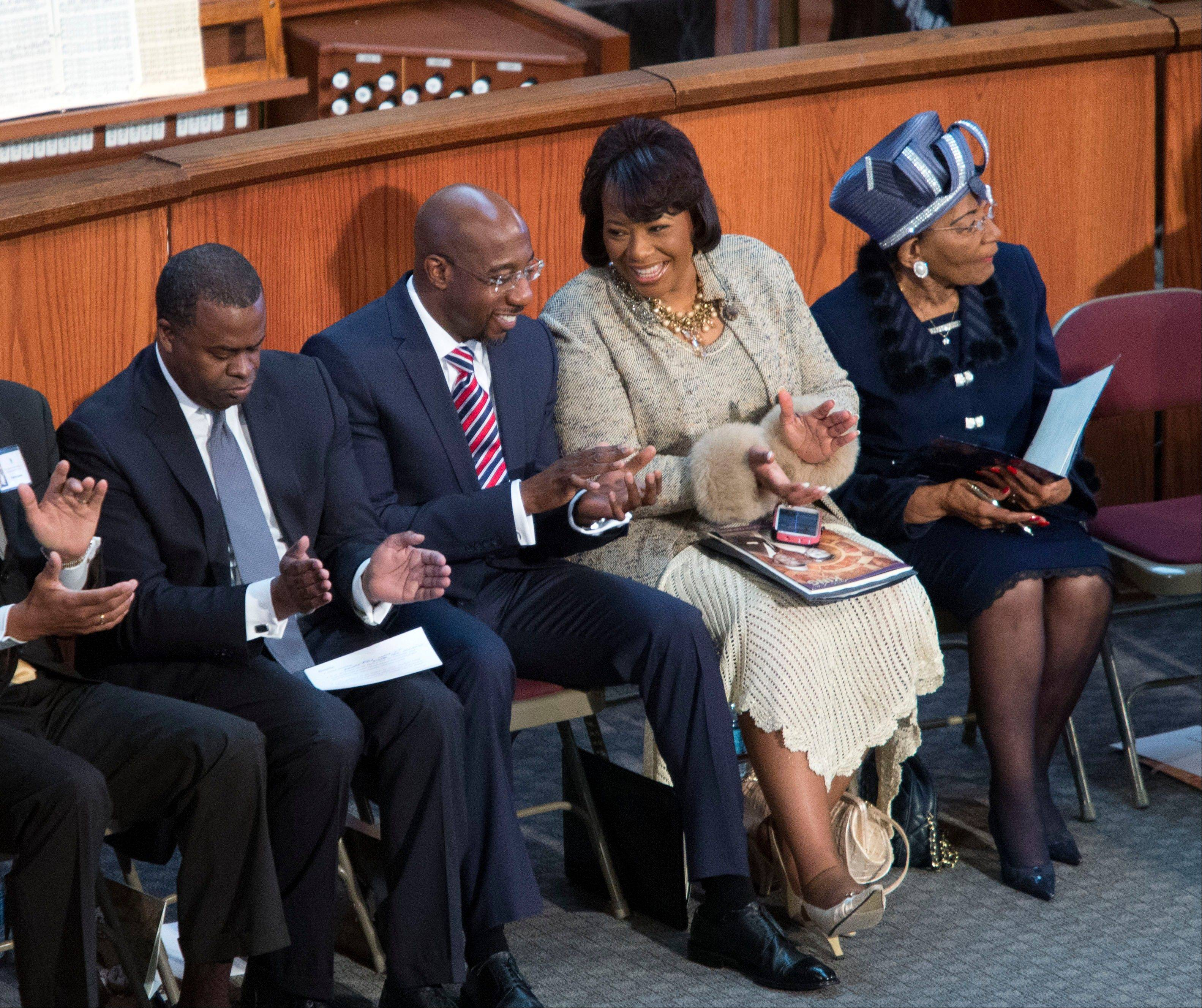 Bernice King, second from right, talks with pastor Raphael Warnock, second from left, during the Rev. Martin Luther King Jr. holiday commemorative service at Ebenezer Baptist Church Monday, Jan. 20, 2014, in Atlanta. Bernice King is the daughter of the late Dr. Martin Luther King Jr., and Christine King Farris, right, is the only living sibling of the late Dr. Martin Luther King Jr.. Also pictured is Atlanta mayor Kasim Reed, left.