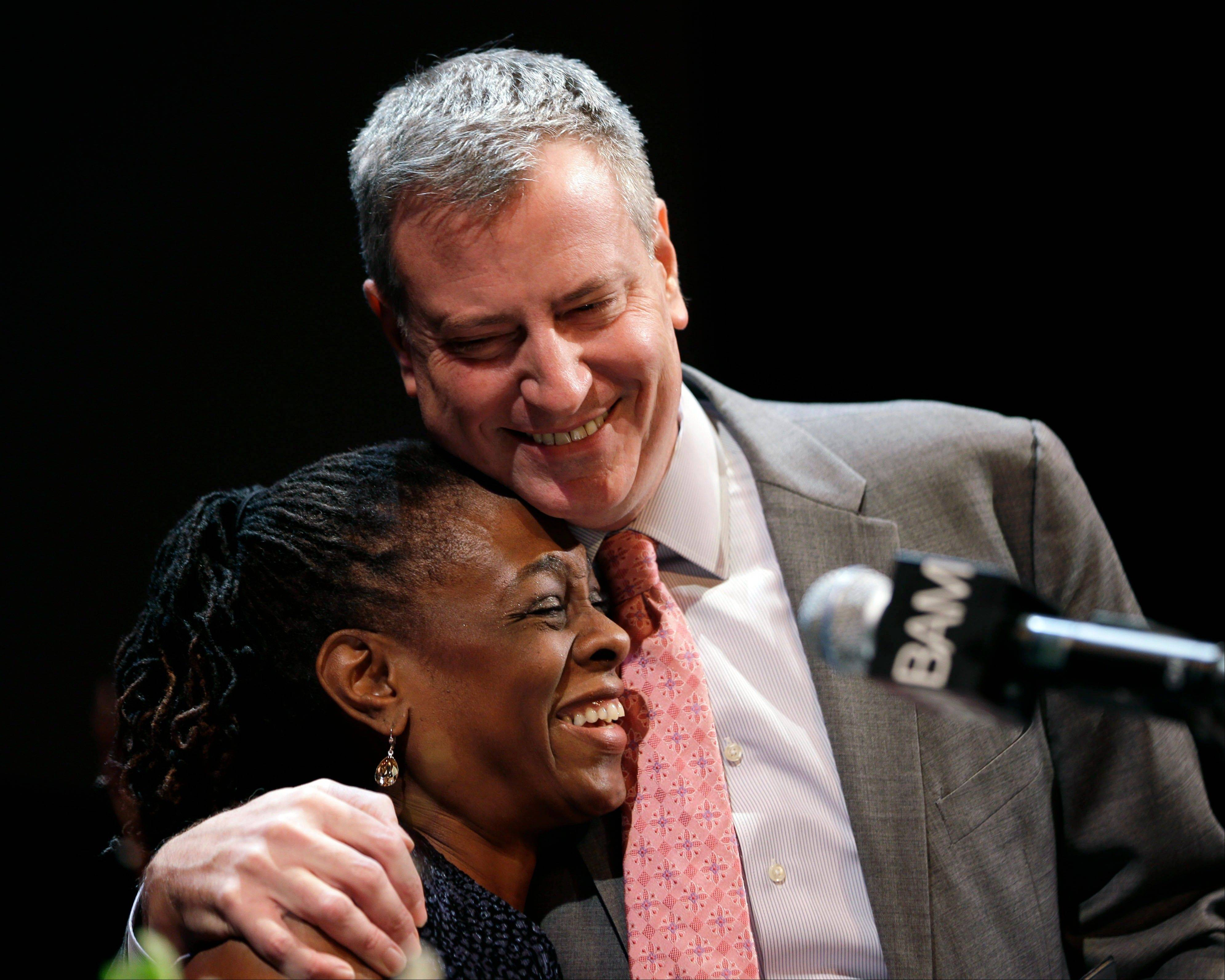 "New York City Mayor Bill de Blasio hugs his wife Chirlane McCray at a tribute to Martin Luther King, Jr. in the Brooklyn borough of New York, Monday, Jan. 20, 2014. De Blasio told a packed audience Monday at the Brooklyn Academy of Music that the ""price of inequality has deepened."" The mayor says economic inequality is closing doors for hard-working people in the city and around the country."