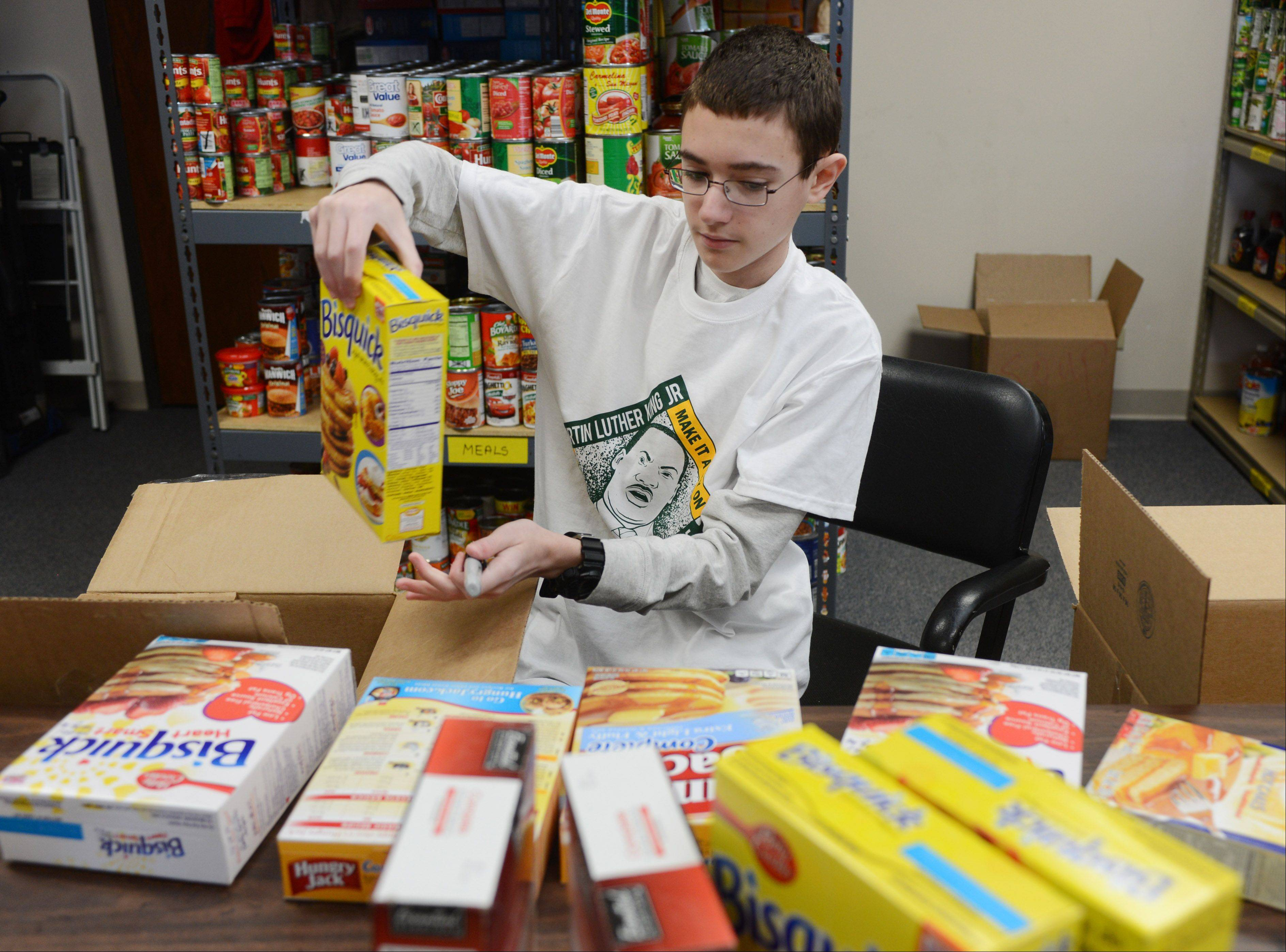 Stevenson High School freshman Matthew Weiner check expiration dates on pancake mixes Monday at the Vernon Township Food Pantry. Stevenson students fanned out over Lake County to work on community projects for Marting Luther King Jr. Day.