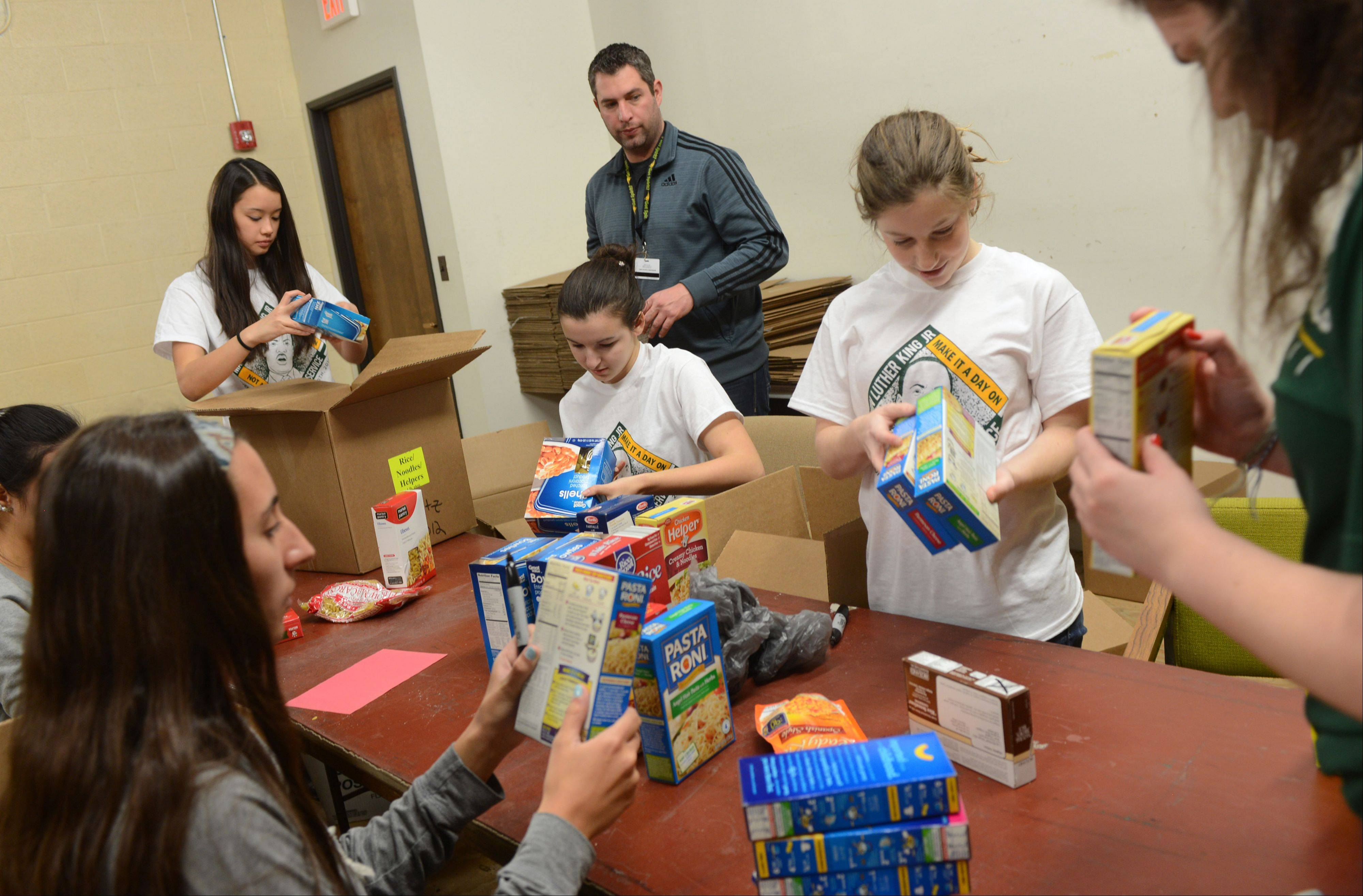 Ted Goergen, director of student activities, works with Stevenson High School students Monday at the Vernon Township Food Pantry on Martin Luther King Jr. Day.
