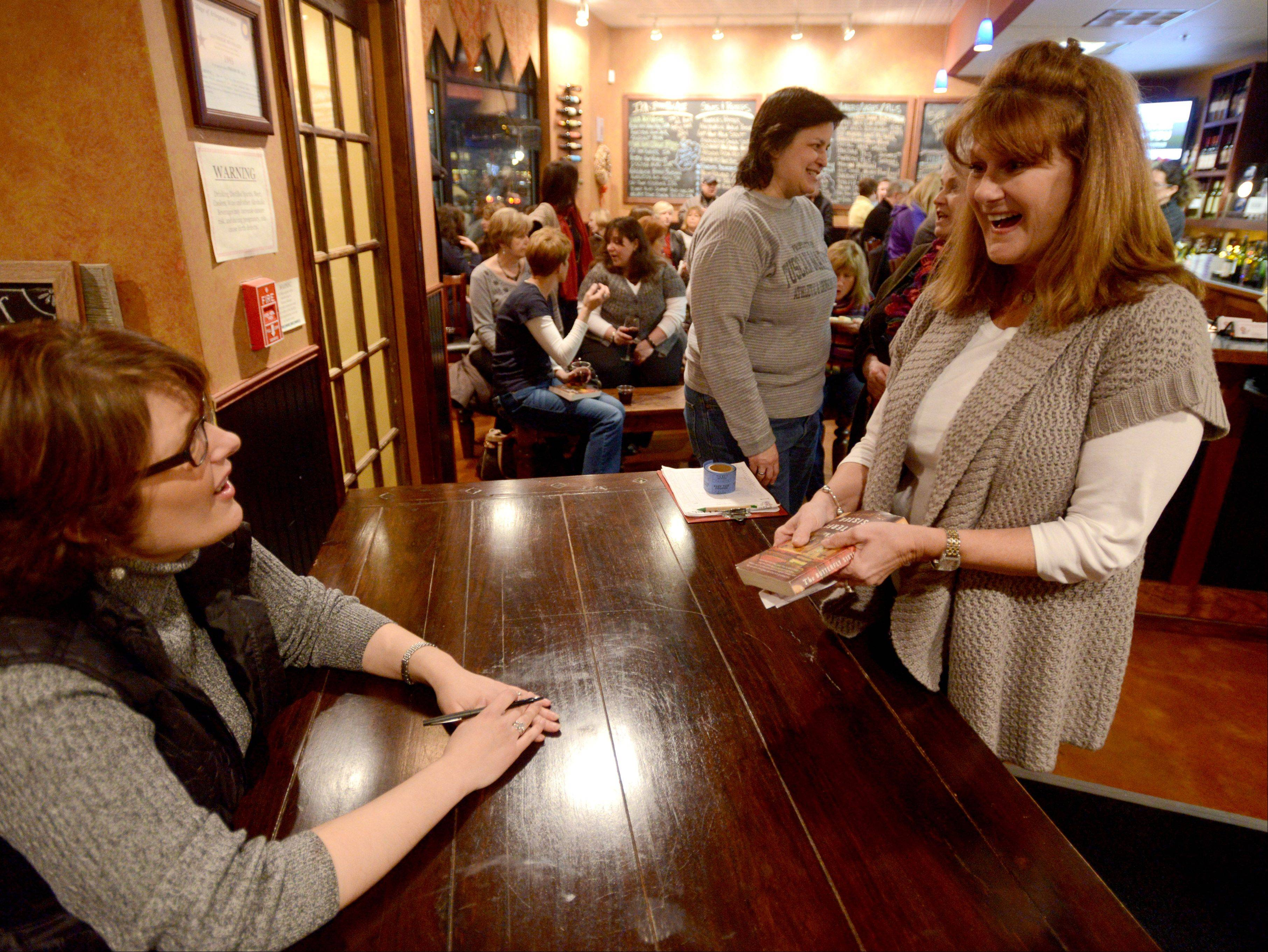 Barb Caputo, right, of Arlington Heights is delighted to get Amy Gail Hansen's signature in a copy of her novel.