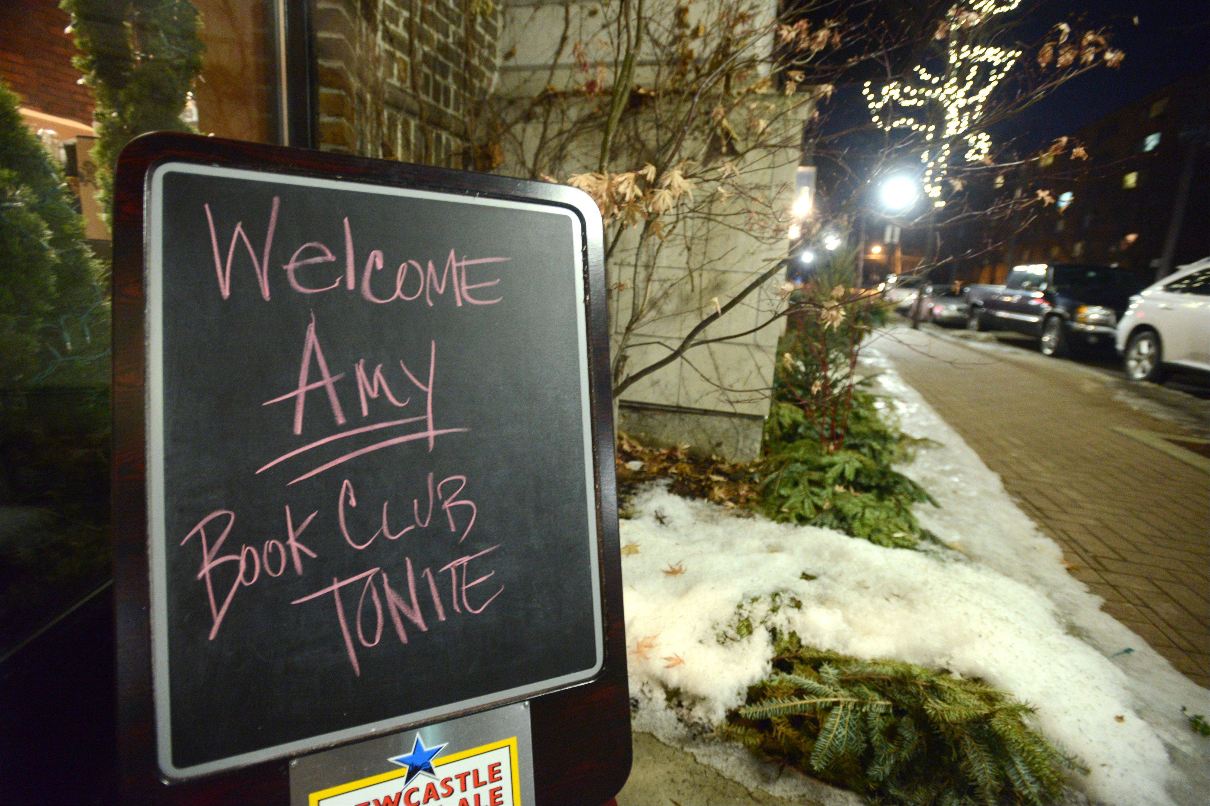 A chalkboard sign greets patrons and author Amy Gail Hansen.