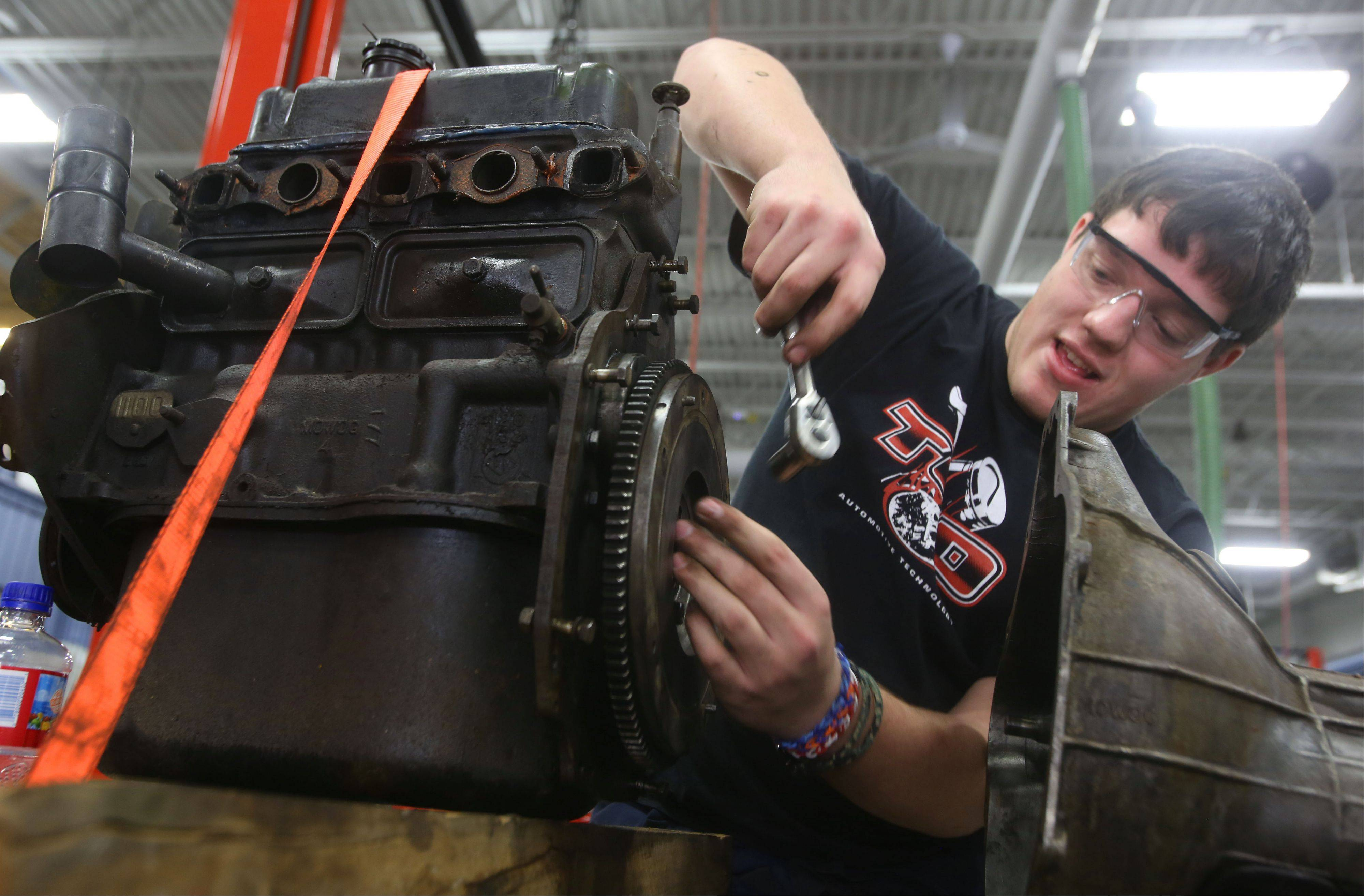 Automotive technology student Nathan Teske from Naperville Central High School works on the flywheel of his 1996 MG Midget in a class at the Technology Center of DuPage. Students are allowed to bring in their own vehicles to work on as long as the work fits what they are studying at the time.