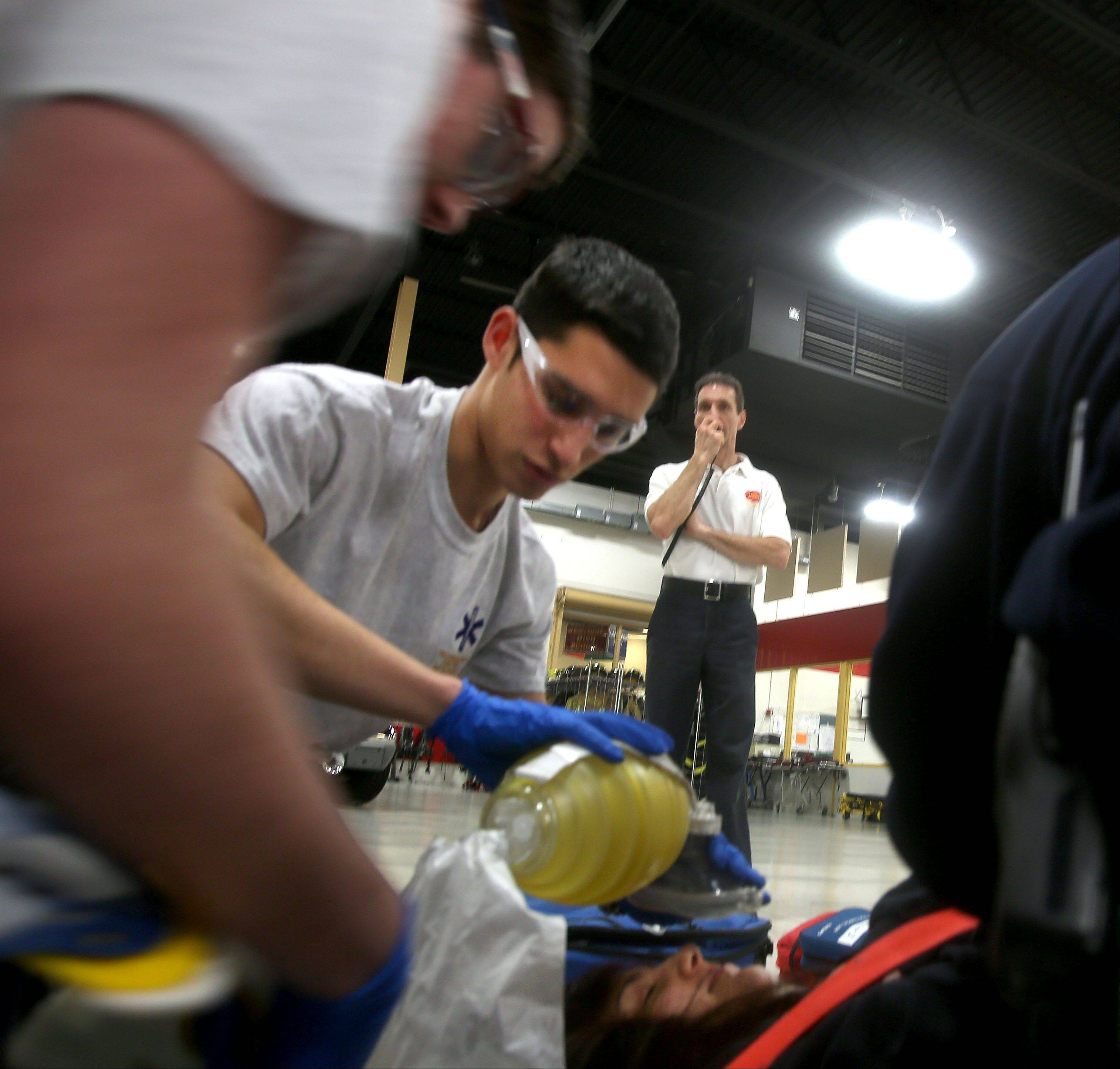 Fire science student Alec Siwek, center, of Naperville participates in a training drill monitored by EMT class instructor Greg Leston.