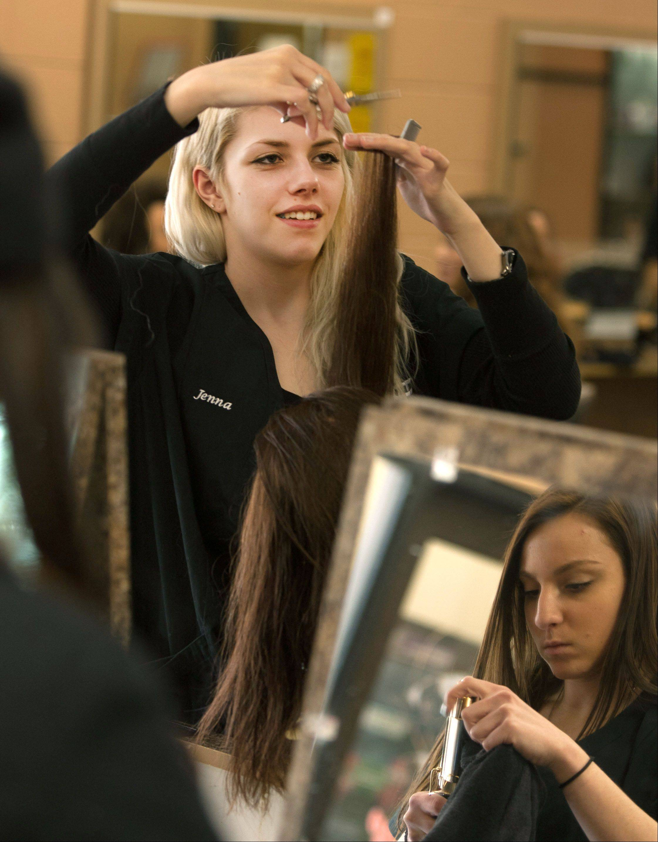 Jenna Strohbusch, left, of Glenbard South High School and Marianna Oddo of Glenbard North High School work on hair in a cosmetology class at the Technology Center of DuPage.