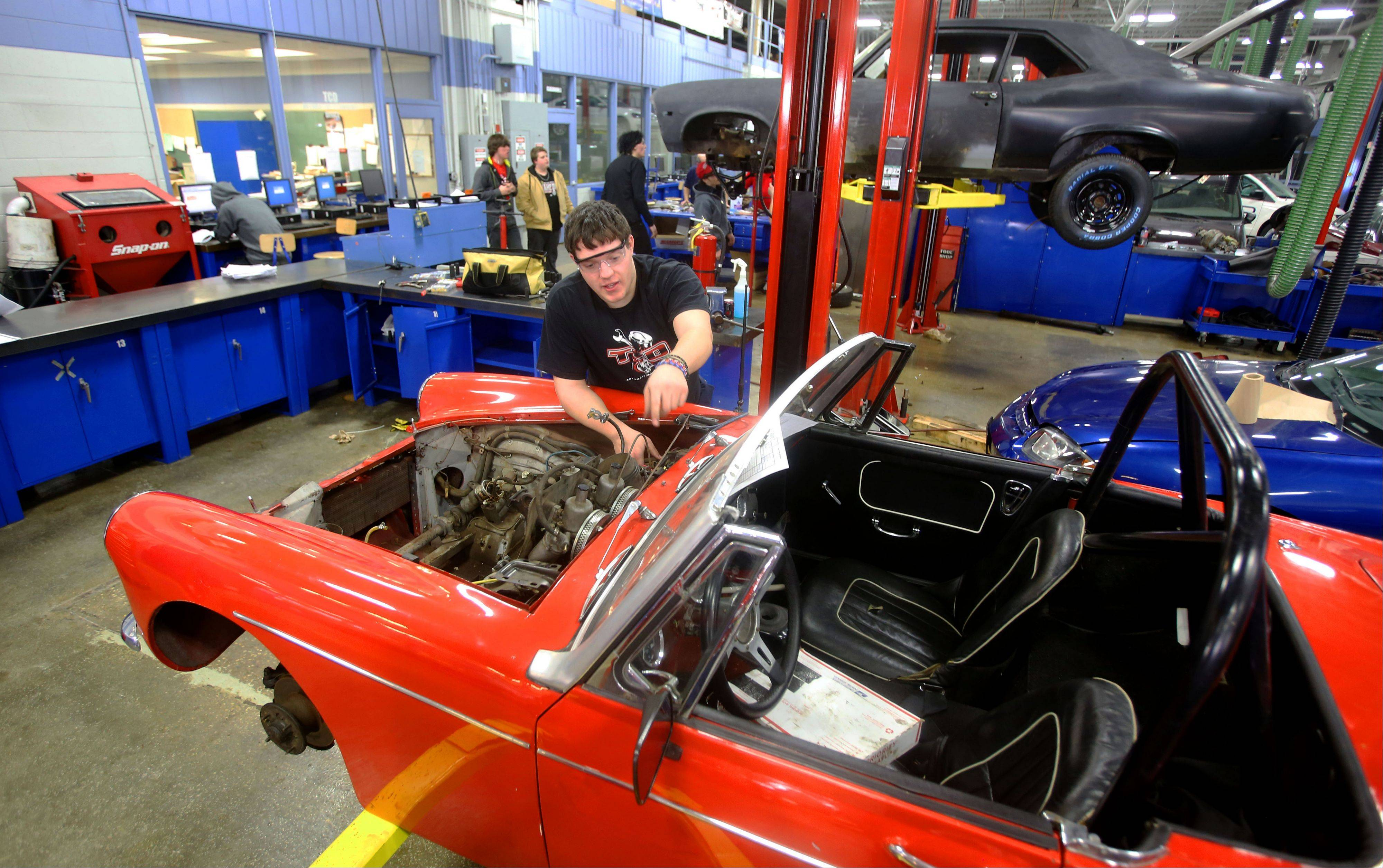 Nathan Teske of Naperville Central works on his 1996 MG Midget. The center also has donated vehicles for students to get hands-on experience diagnosing problems that the instructors have created. Area residents can have students work on their cars and are charged only for parts.