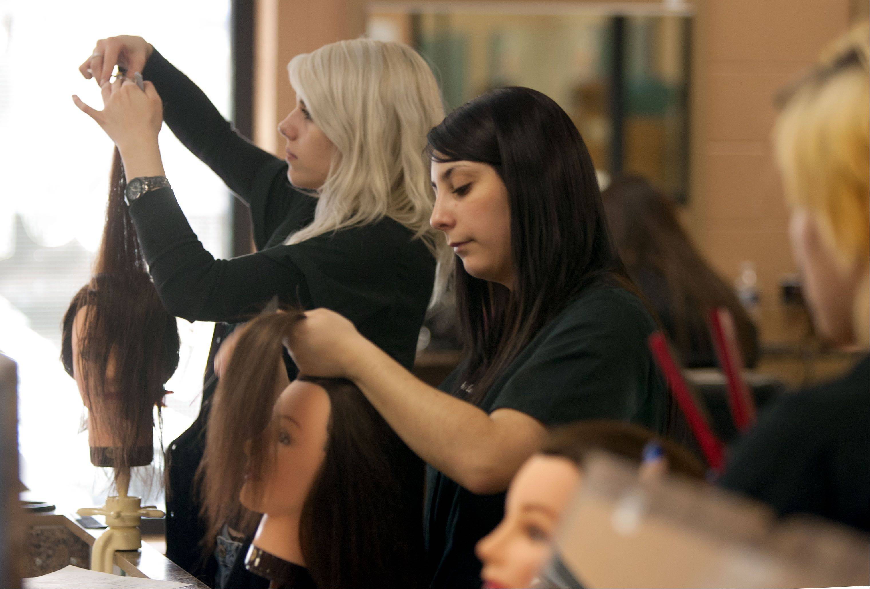 Jenna Strohbusch of Glenbard South High School, left, and Marianna Oddo of Glenbard North High School, work on hair during a cosmetology class at Technology Center of DuPage.