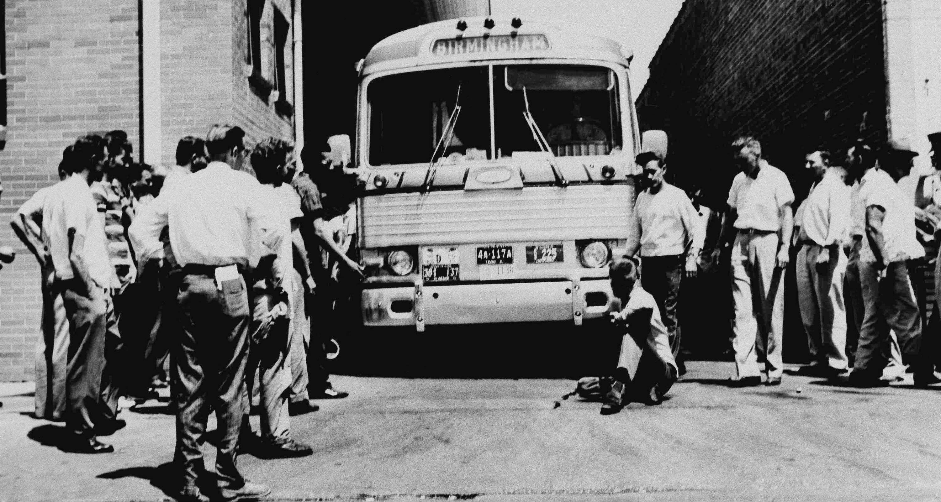 An unidentified man sits in front of a Greyhound bus of Freedom Riders to prevent it from leaving the station in Anniston, Ala., May 15, 1961. The bus was surrounded outside Anniston and burned.