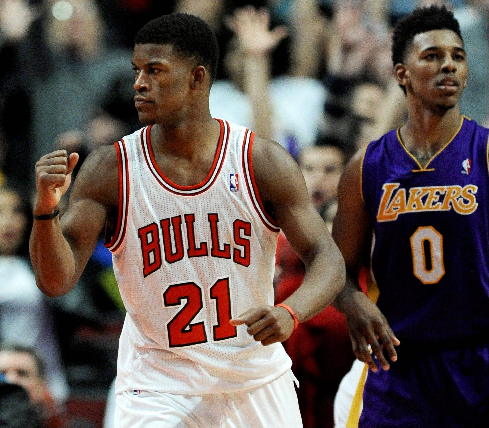 The Bulls' Jimmy Butler celebrates while Los Angeles Lakers' Nick Young looks on after Taj Gibson made the game-winning shot in overtime to defeat the Lakers 102-100 during an NBA basketball game in Chicago, Monday, Jan. 20, 2014.