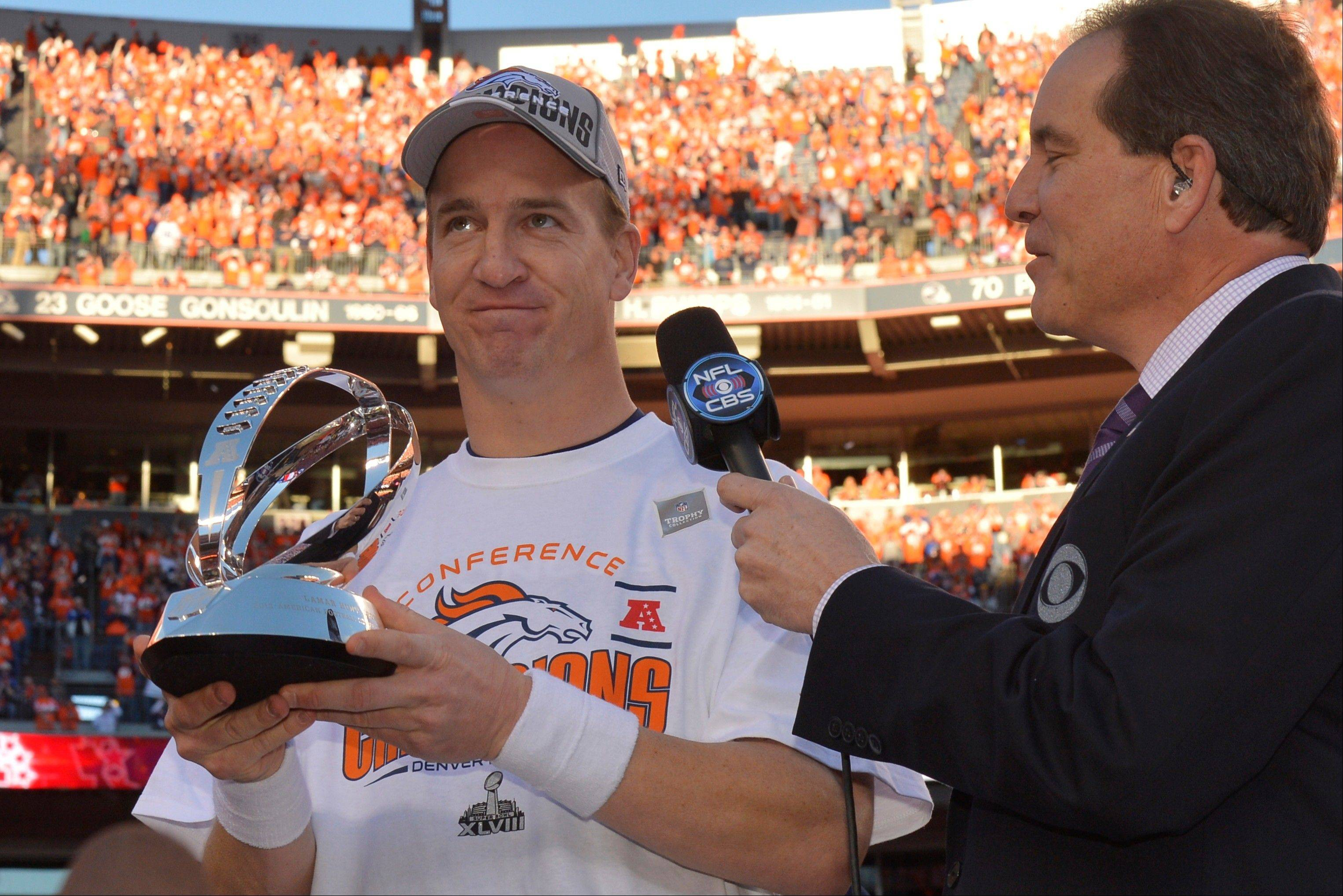 Denver Broncos quarterback Peyton Manning, left, holds the trophy after the AFC Championship NFL playoff football game against the New England Patriots in Denver, Sunday, Jan. 19, 2014. The Broncos defeated the Patriots 26-16 to advance to the Super Bowl.