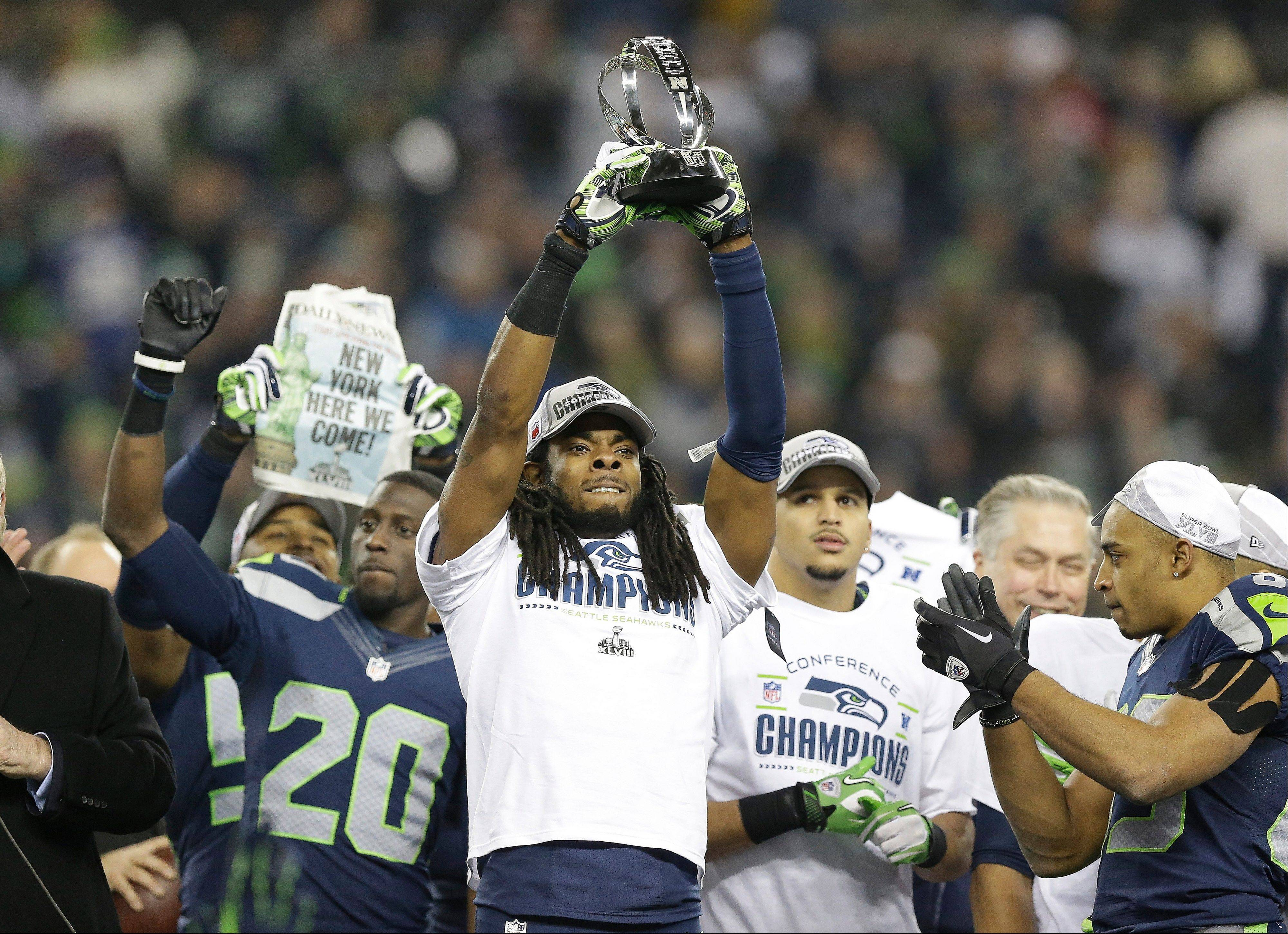 Seattle Seahawks' Richard Sherman holds up the George Halas Trophy after the NFL football NFC Championship game against the San Francisco 49ers Sunday, Jan. 19, 2014, in Seattle. The Seahawks won 23-17 to advance to Super Bowl XLVIII.