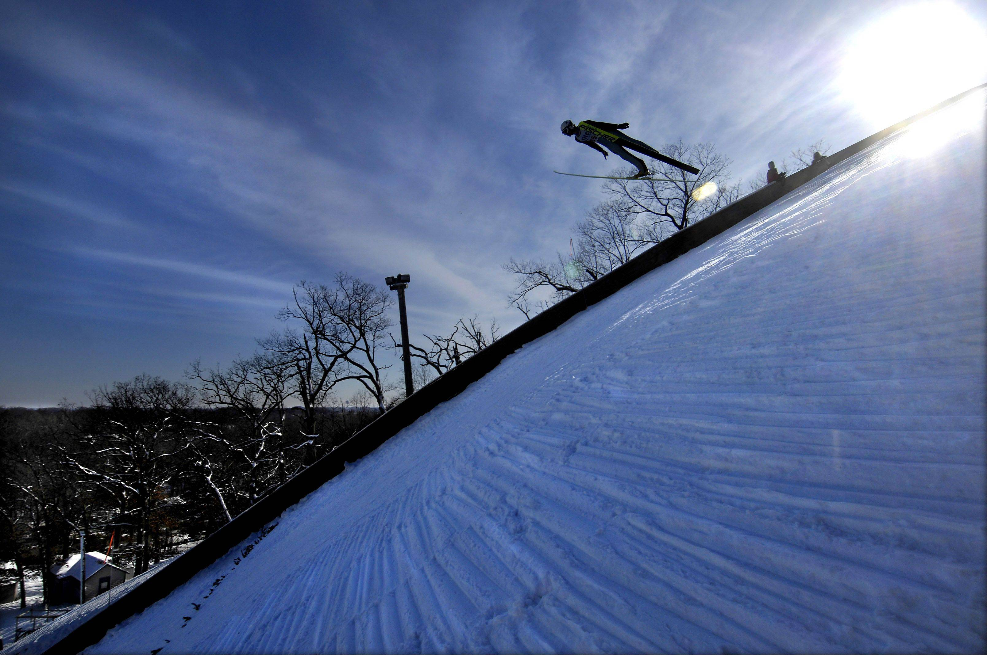 "The packed snow on the 70 meter ski jump hill reflects the blue winter sky as a skier sails down at a previous Norge Ski Jump Tournament in Fox River Grove. Dozens of former and potential Olympic ski jumpers compete at the event. The hills and jumps are all built and maintained by volunteers. More than 100 years ago, Norge Ski Club members carried snow up onto the tower by using long lines of volunteers, passing bags of snow from one person to the next, and spreading it on the tower and hill by hand. Today it is still done the same way. In the days before the weekend tournament, the ""snowing the tower"" chore is a social event for the club."