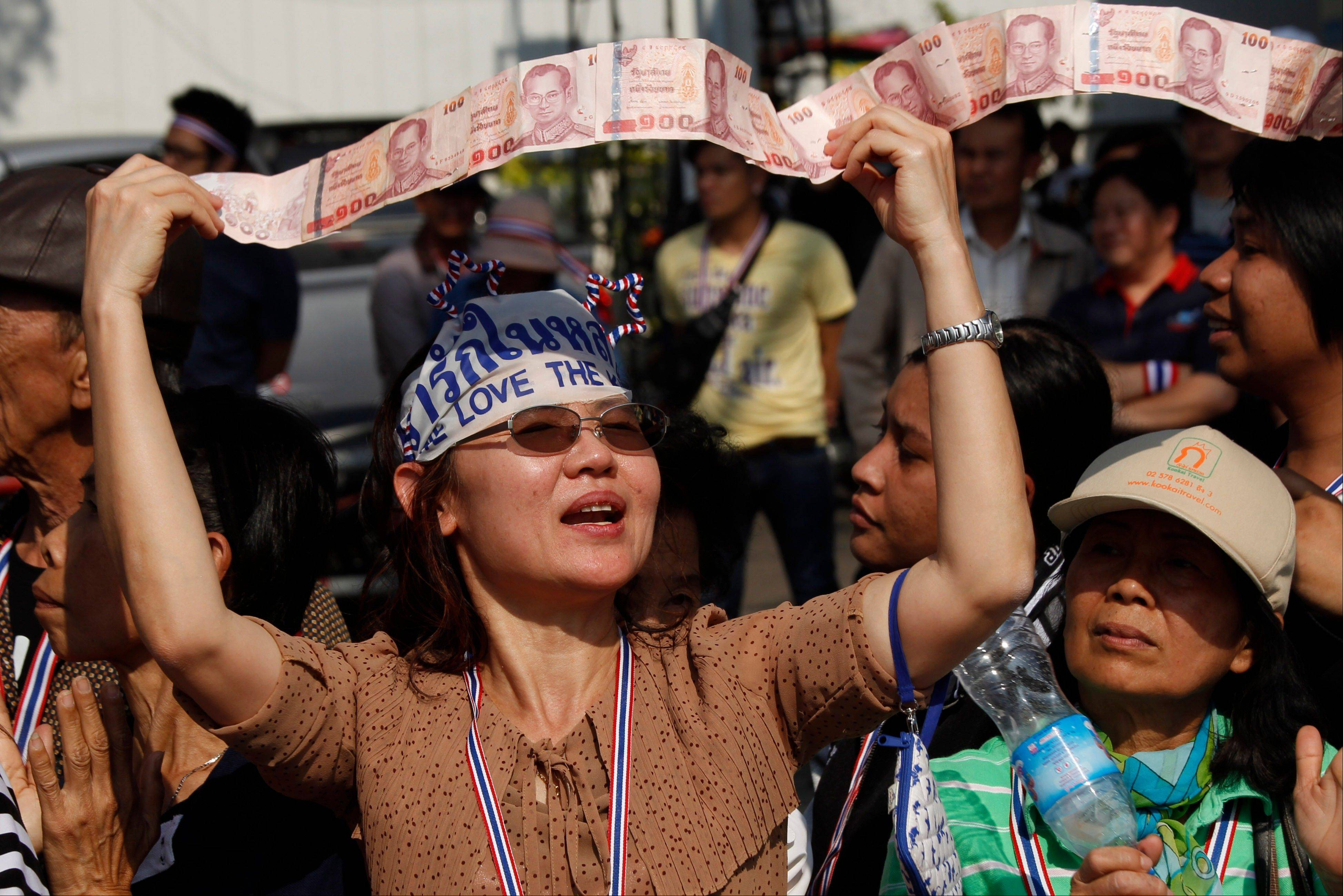 An anti-government supporter displays her donations for the cause during a street rally in central Bangkok, Thailand, Tuesday, Jan. 21, 2014. Thailand has declared a state of emergency in Bangkok and its surrounding areas to cope with anti-government protests that have stirred up violent attacks.