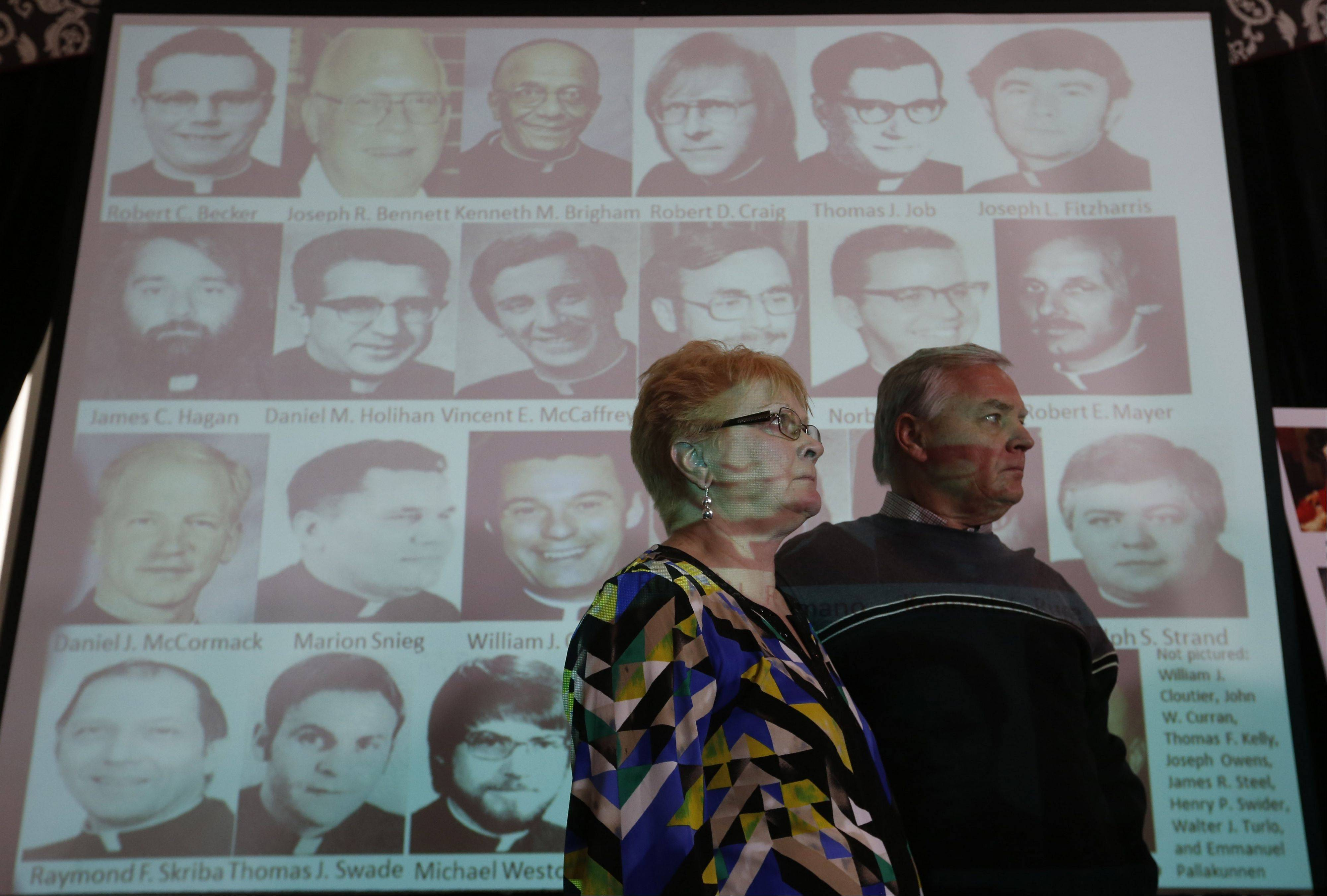 Kathy and Jim Laarveld, of Wheeling, whose son was sexually abused by a priest, stand before projected photos of some priests identified as abusers during a news conference Tuesday, where thousands of files were released about priests in the Archdiocese of Chicago sexually abusing minors.