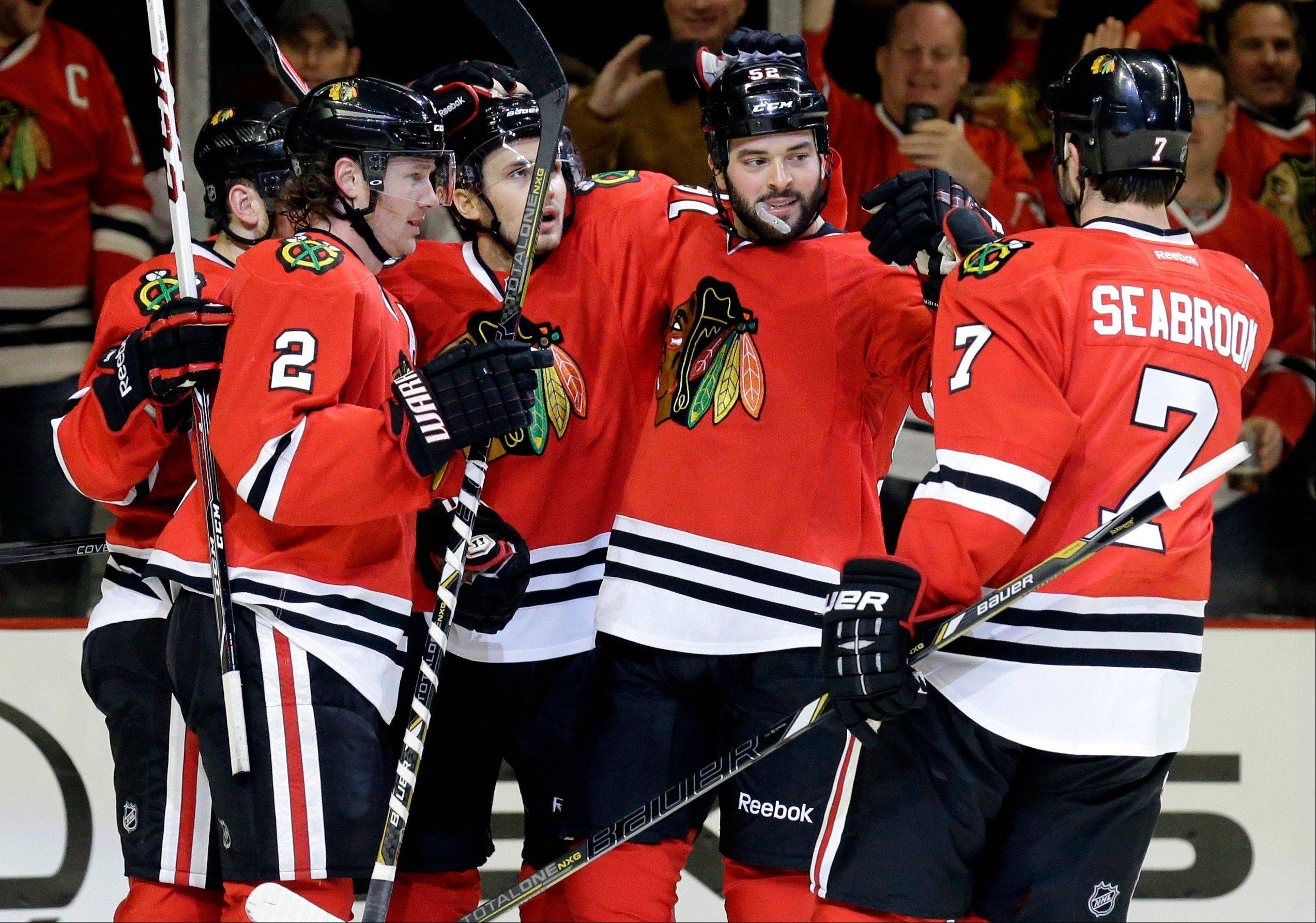 Brandon Bollig, second from right, celebrates with teammates after scoring a goal in Sunday�s victory over Boston. Bollig says the Hawks are excited about Wednesday night�s meeting with the Red Wings at Detroit.