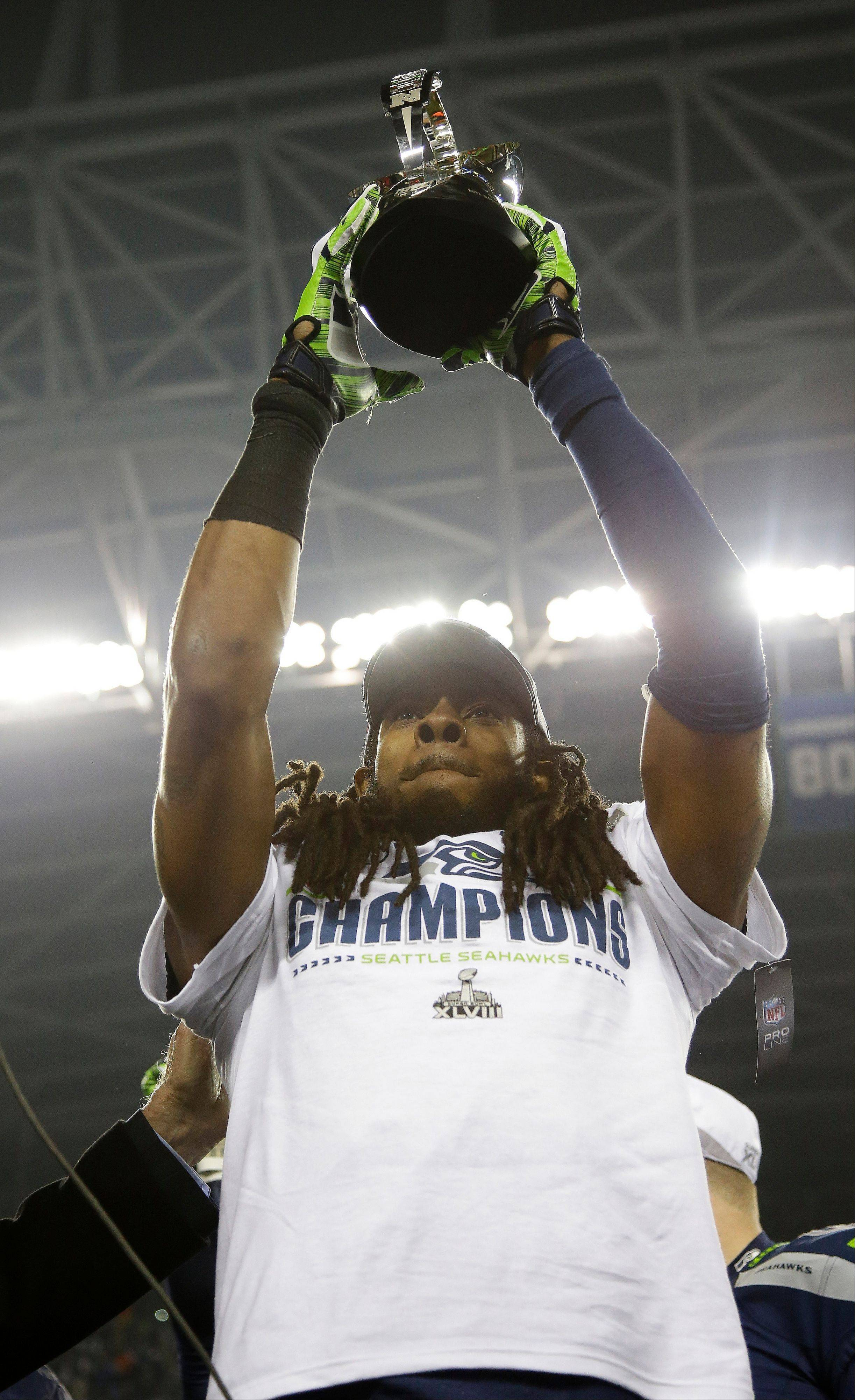 Seattle�s Richard Sherman holds up the George Halas Trophy after the NFC Championship Game against the San Francisco 49ers on Sunday. The Seahawks won 23-17 to advance to Super Bowl XLVIII.