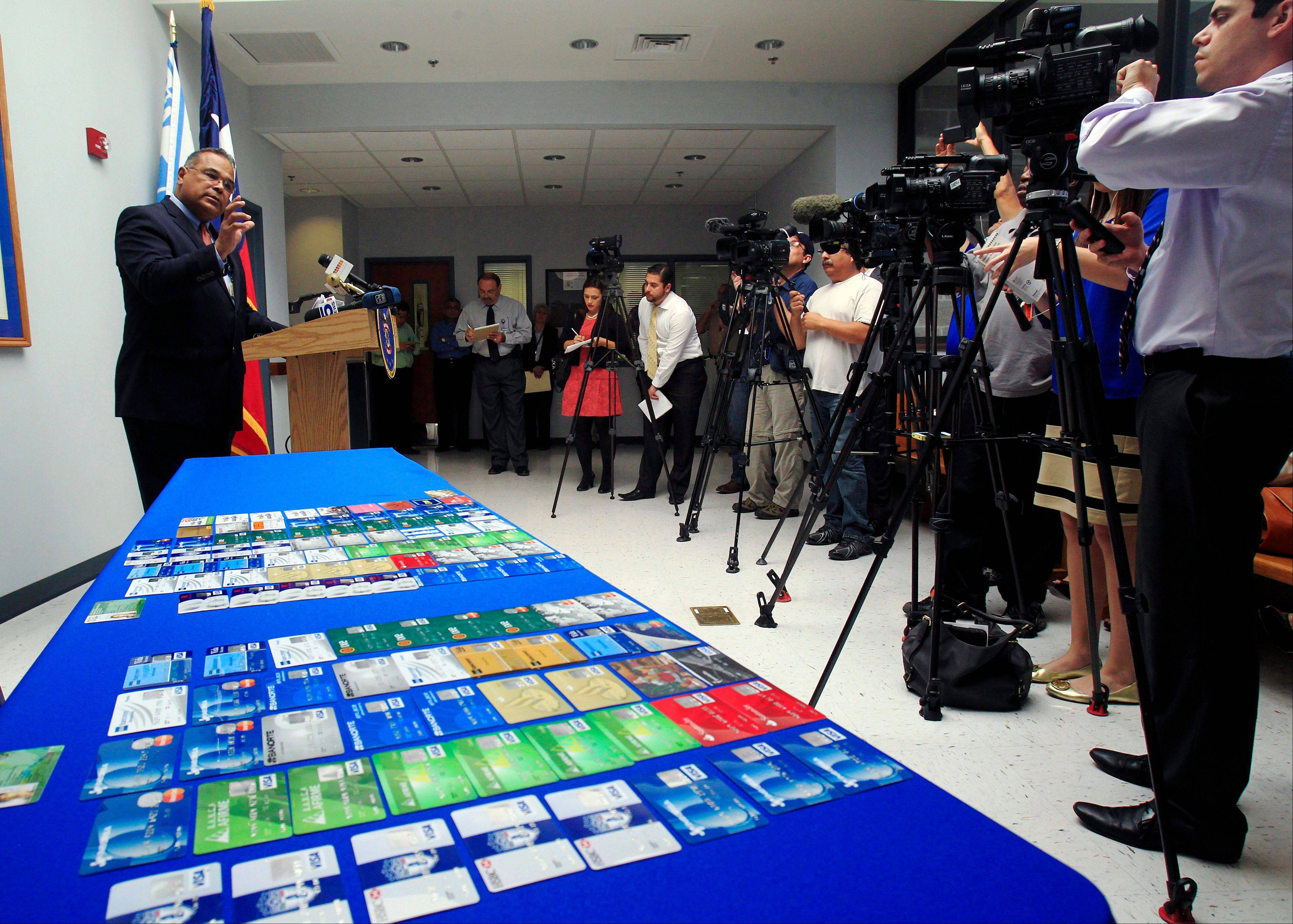 McAllen Police Chief Victor Rodriguez talks to media next to a dozens of fraudulent credit cards that were confiscated by McAllen police after arresting a man and a woman on fraud charges tied to the December Target credit card breach, Monday.