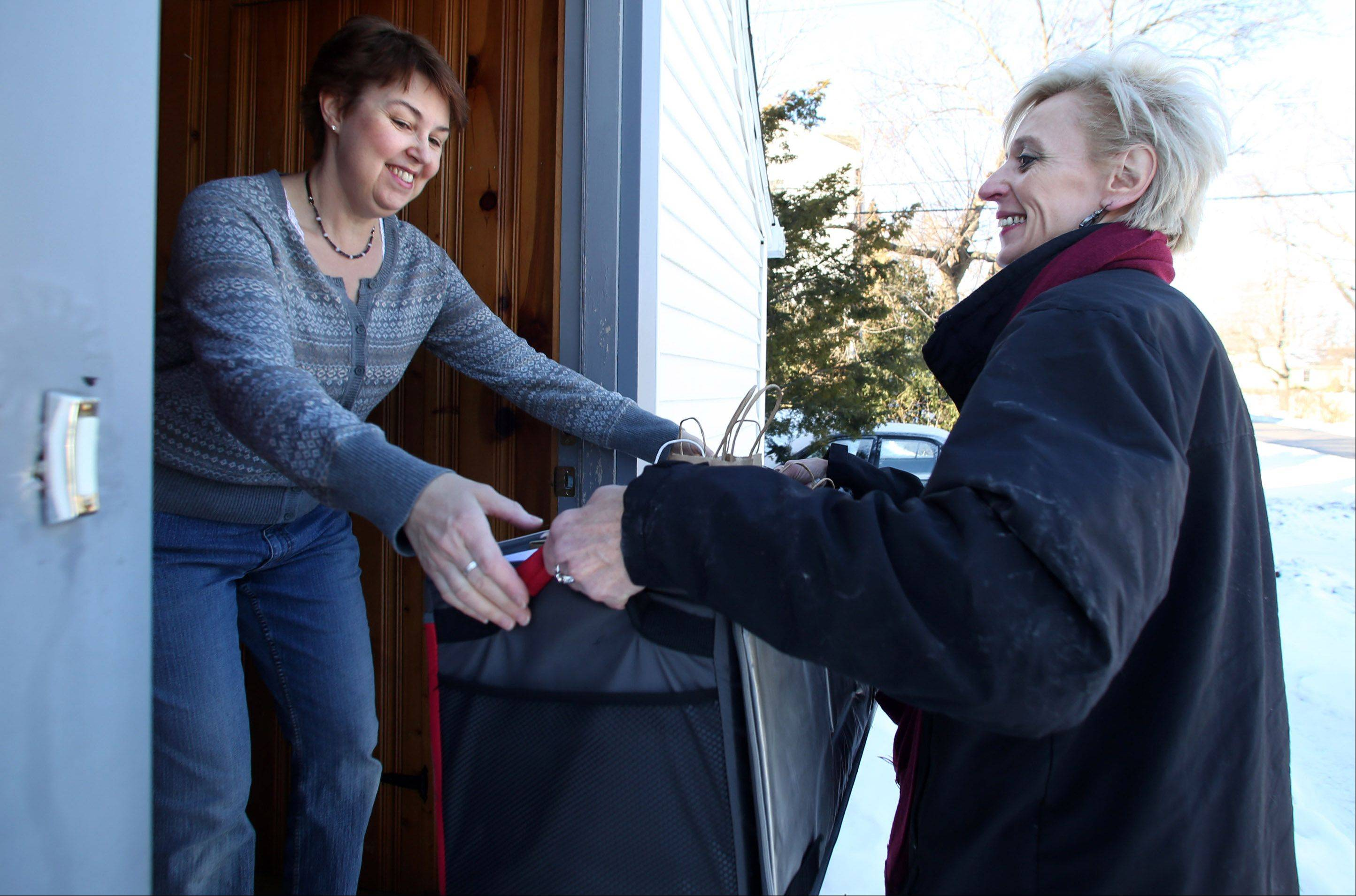 Donna Koranek of Lake Zurich, left, ordered groceries online from Artizone and gets her delivery from Doreen Melchiorre.