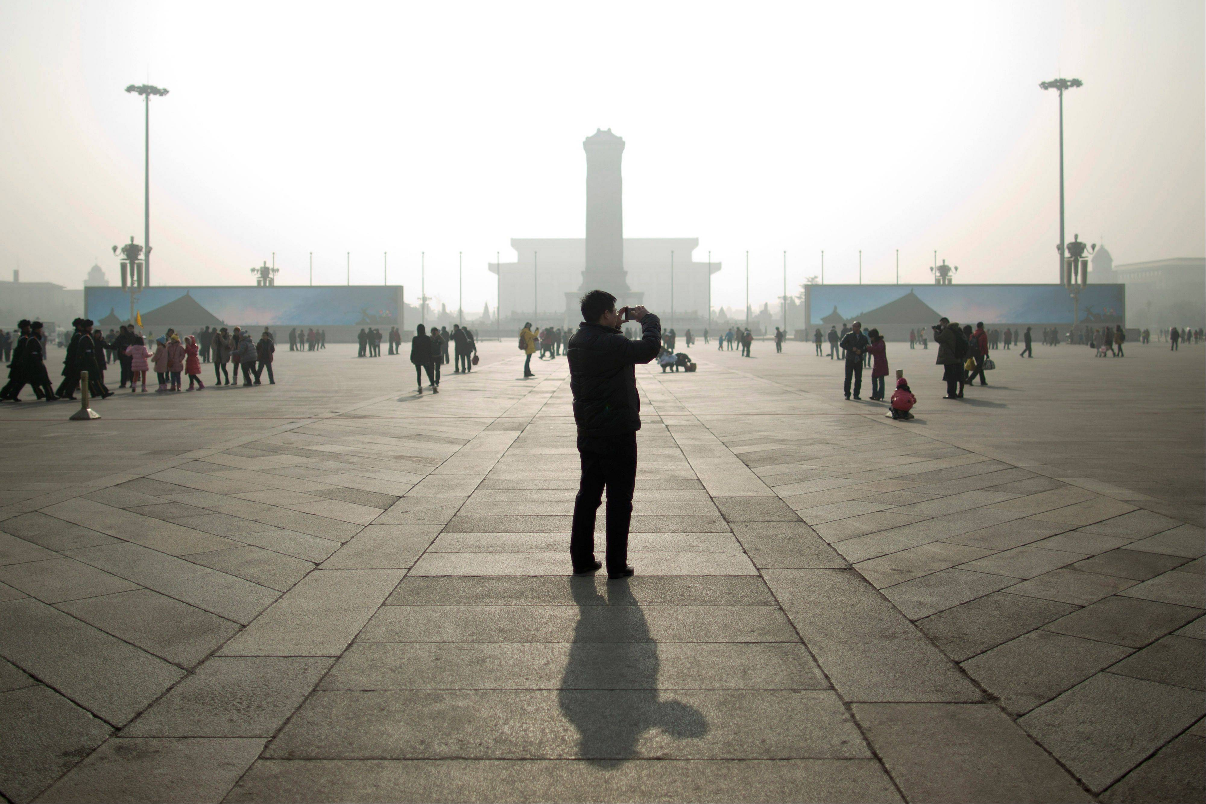 A tourist takes photos during a heavily polluted day on Tiananmen Square in Beijing last week.