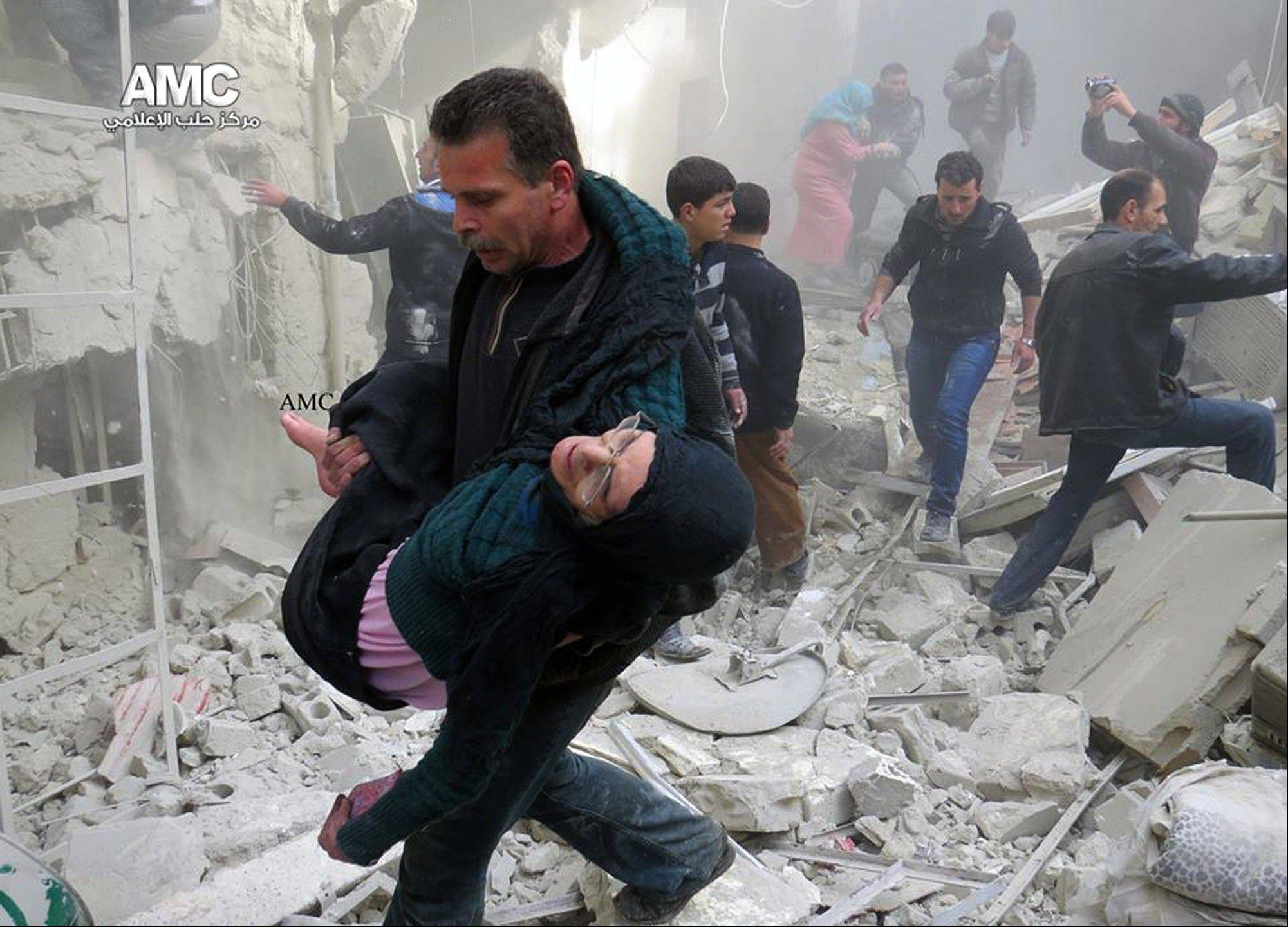 A Syrian man carries an injured woman from a destroyed building which was attacked by Syrian forces warplanes in Aleppo, Syria.