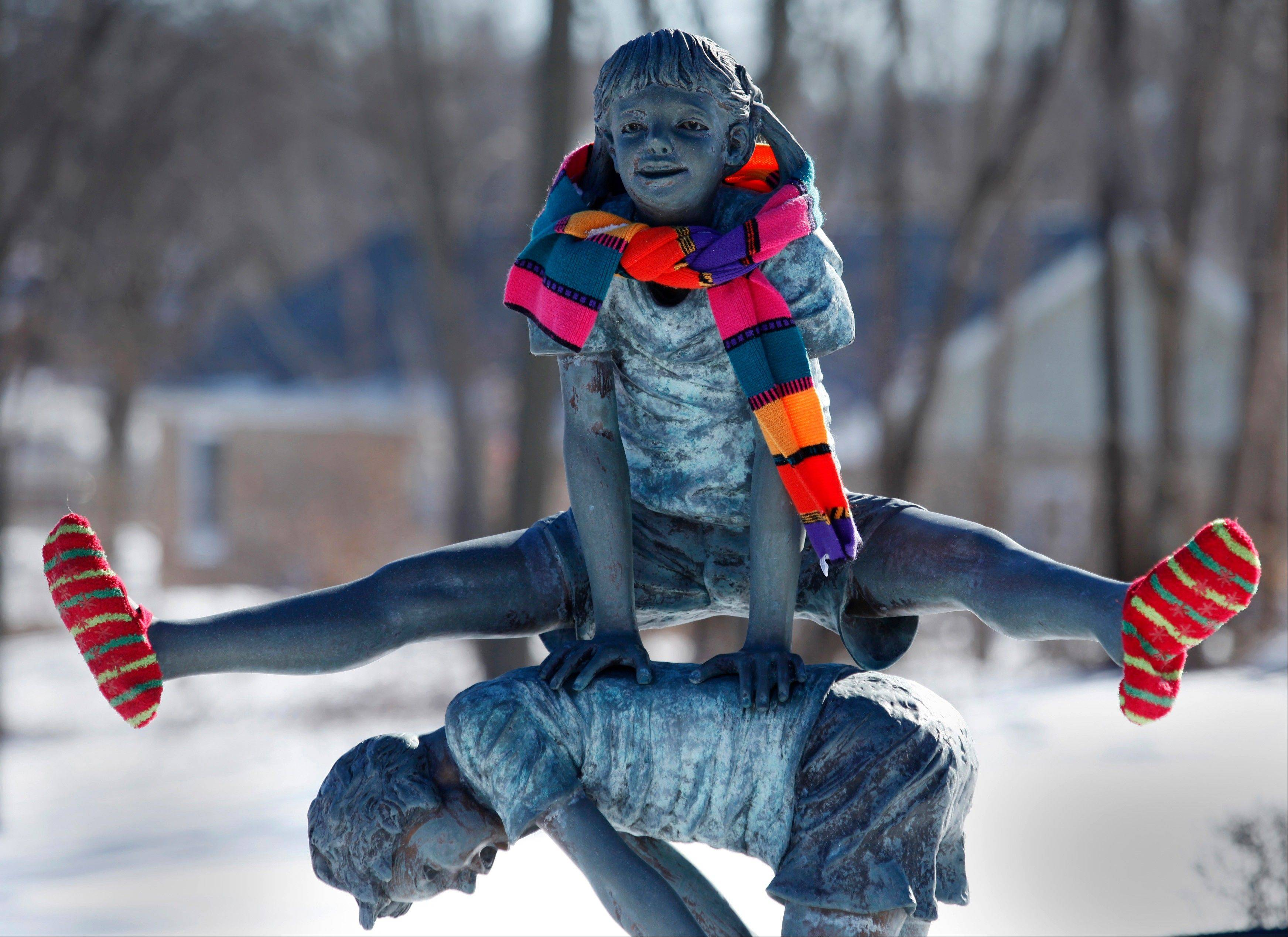 "CHRIS HANKINS/chankins@dailyherald.comThe ""Footprints in Time"" statue is seen dressed in winter attire in South Elgin on Tuesday. The monument, placed in 2007 is dedicated ""to the memory of children whose shortened lives left an eternal impression in the community, and to individuals whose lives were devoted to loving, mentoring and educating them."""