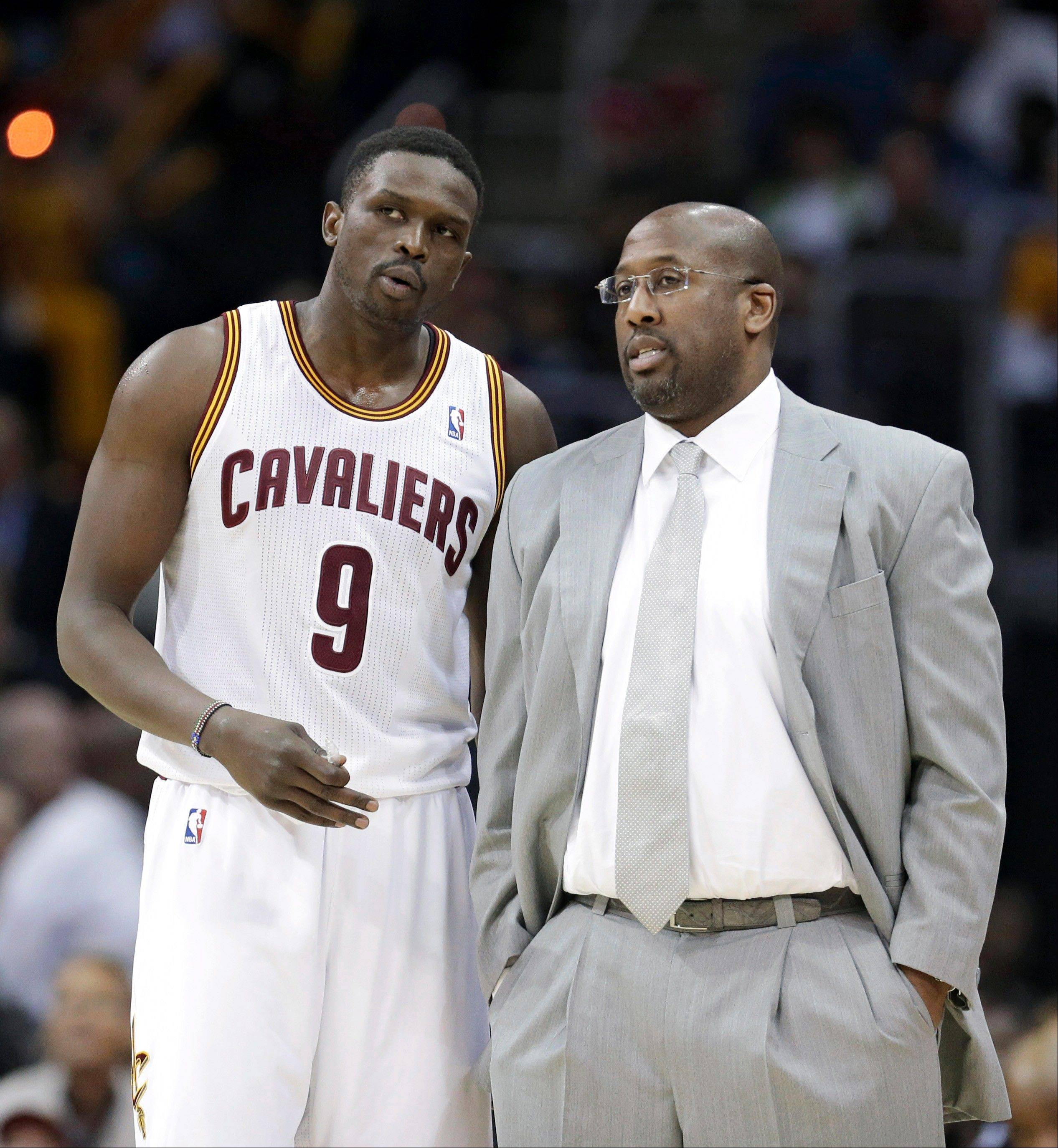 Cleveland Cavaliers head coach Mike Brown, right, talks with Luol Deng during the third quarter of an NBA basketball game, Monday, Jan. 20, 2014, in Cleveland. Dallas defeated Cleveland 102-97.