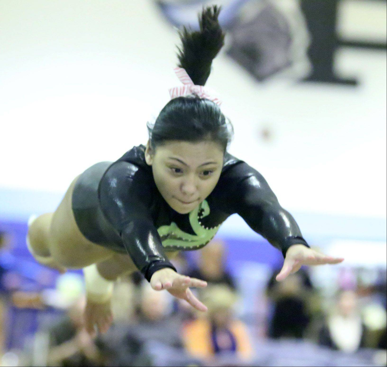 Elk Grove's Inah Enolva competes on the vault during Saturday's girls gymnastics invitational in Mount Prospect.