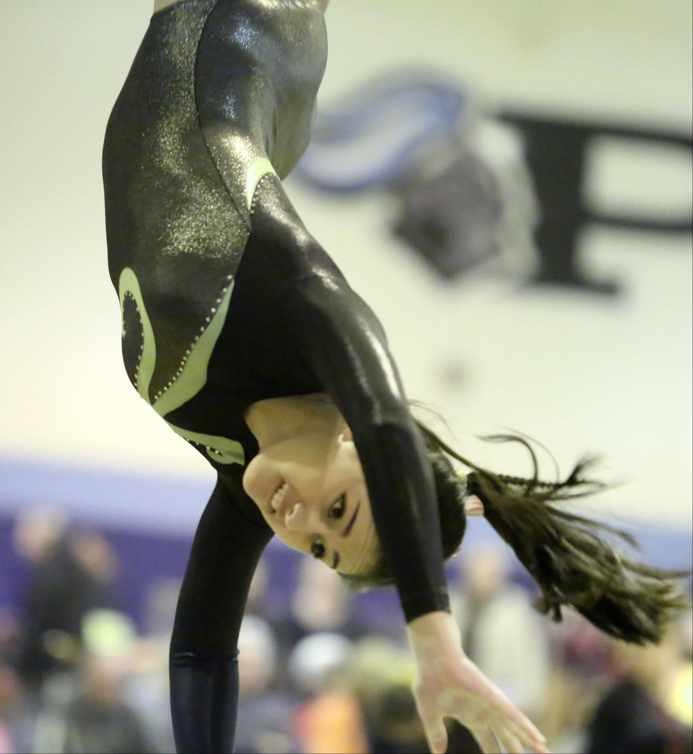 Elk Grove's Mia Loxley competes on the vault during Saturday's girls gymnastics invitational in Mount Prospect.