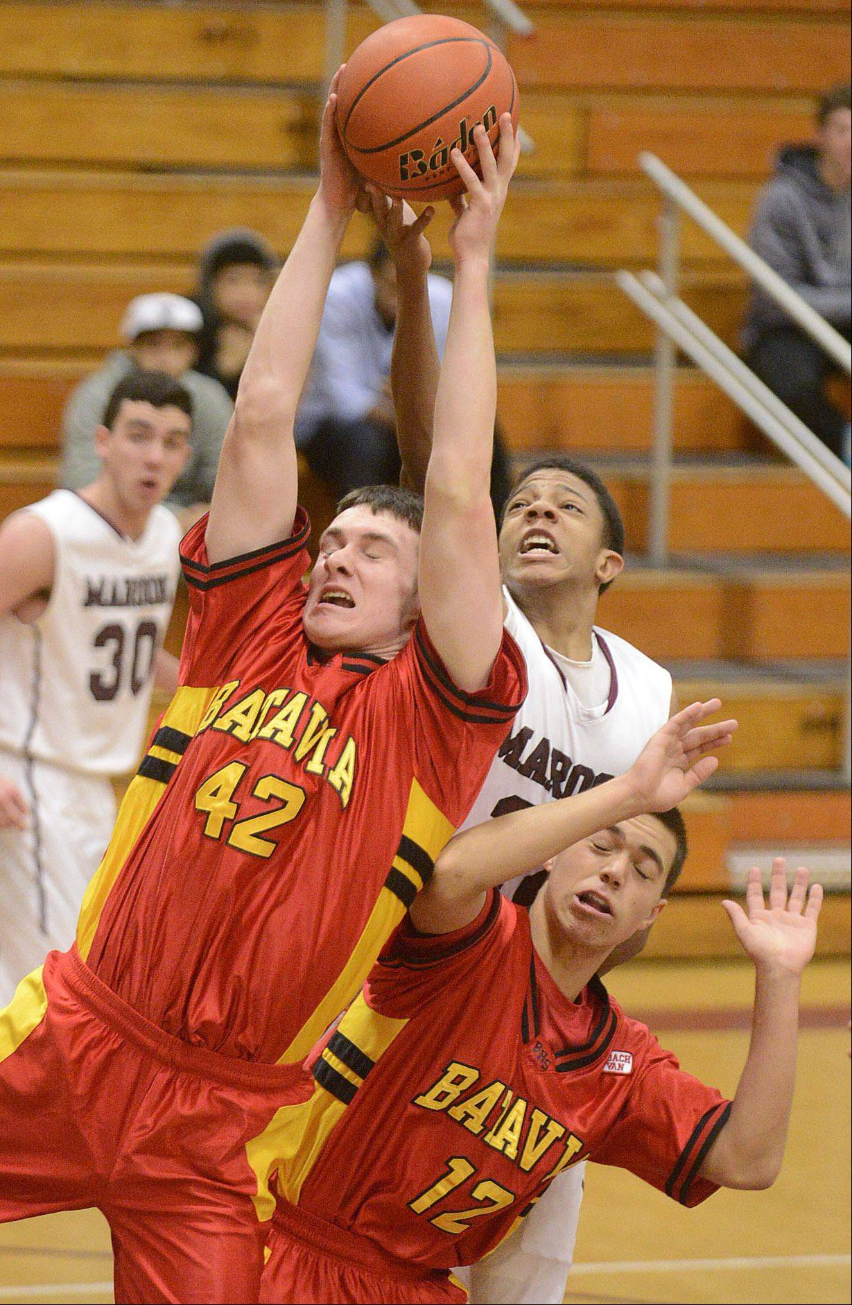 Batavia's Ryan Olson (42) and Elgin's Donte Harper leap for a rebound over Batavia's Canaan Coffey (12) during Saturday's game.