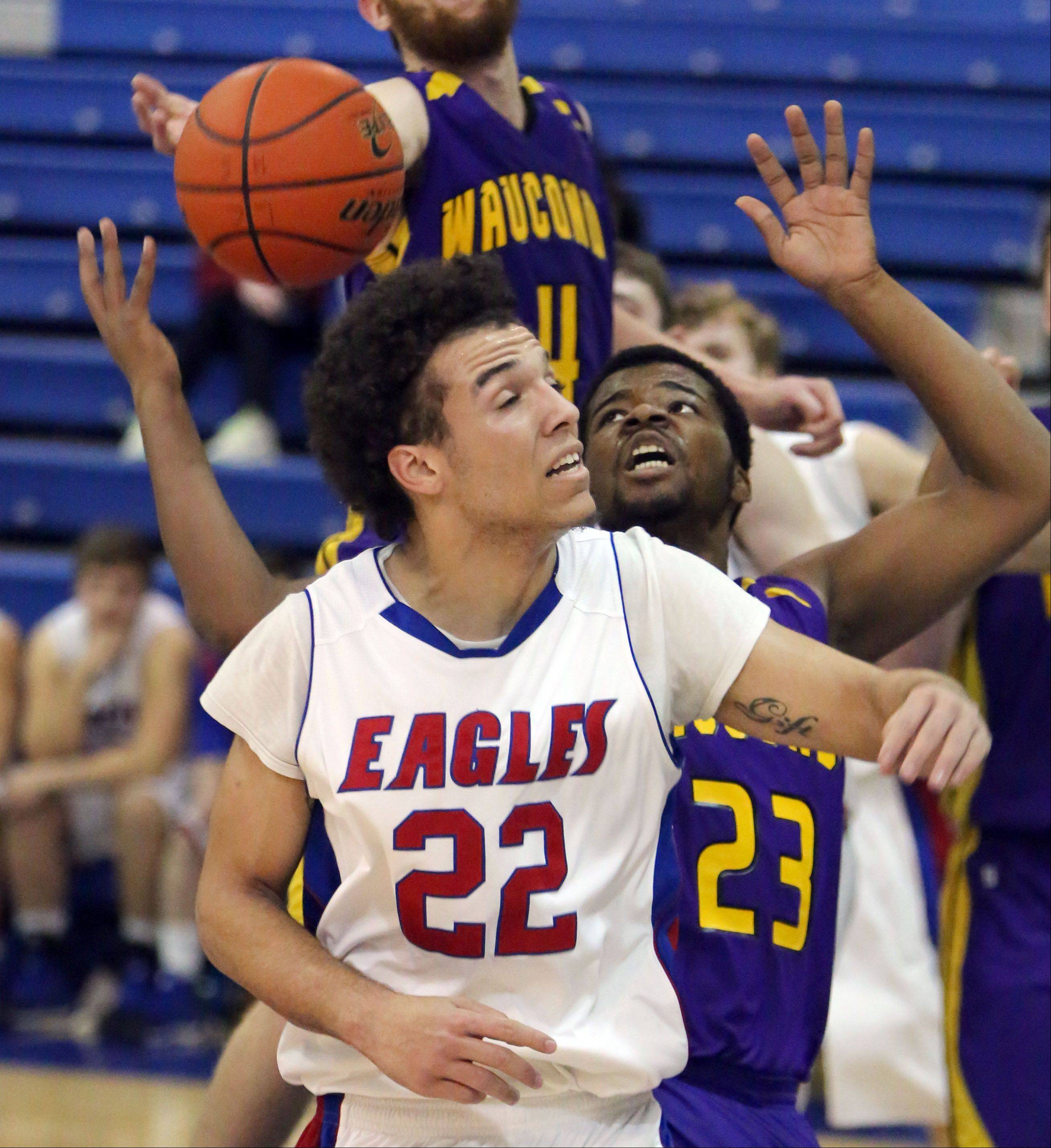 Lakes' Tramone Hudson, left, and Wauconda's Dion Head track down a rebound during Tuesday's game in Lake Villa.