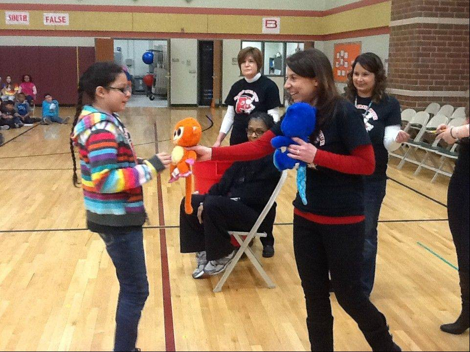 Prairie Trail School student Carolina Carlson receives a raffle prize from teacher Kathy Kibitlewski as part of a recent celebration.
