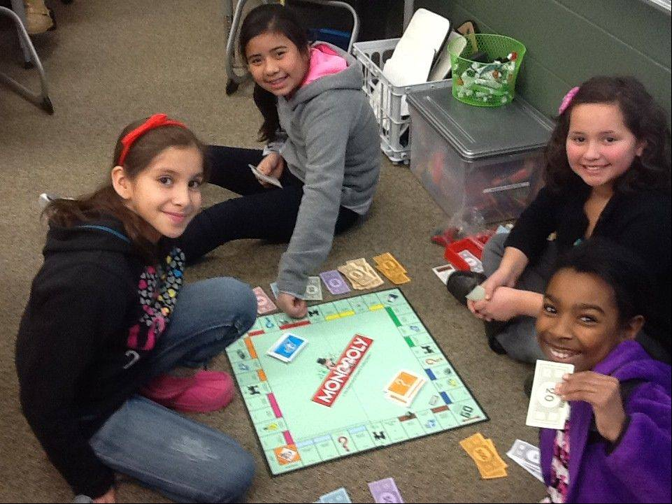 "Students, from left, Aaliyah Gomez, Lizzy Zagata, Michelle Alaniz and Kayla Deere play ""Monopoly"" as part of a recent celebration at Prairie Trail School in Wadsworth."