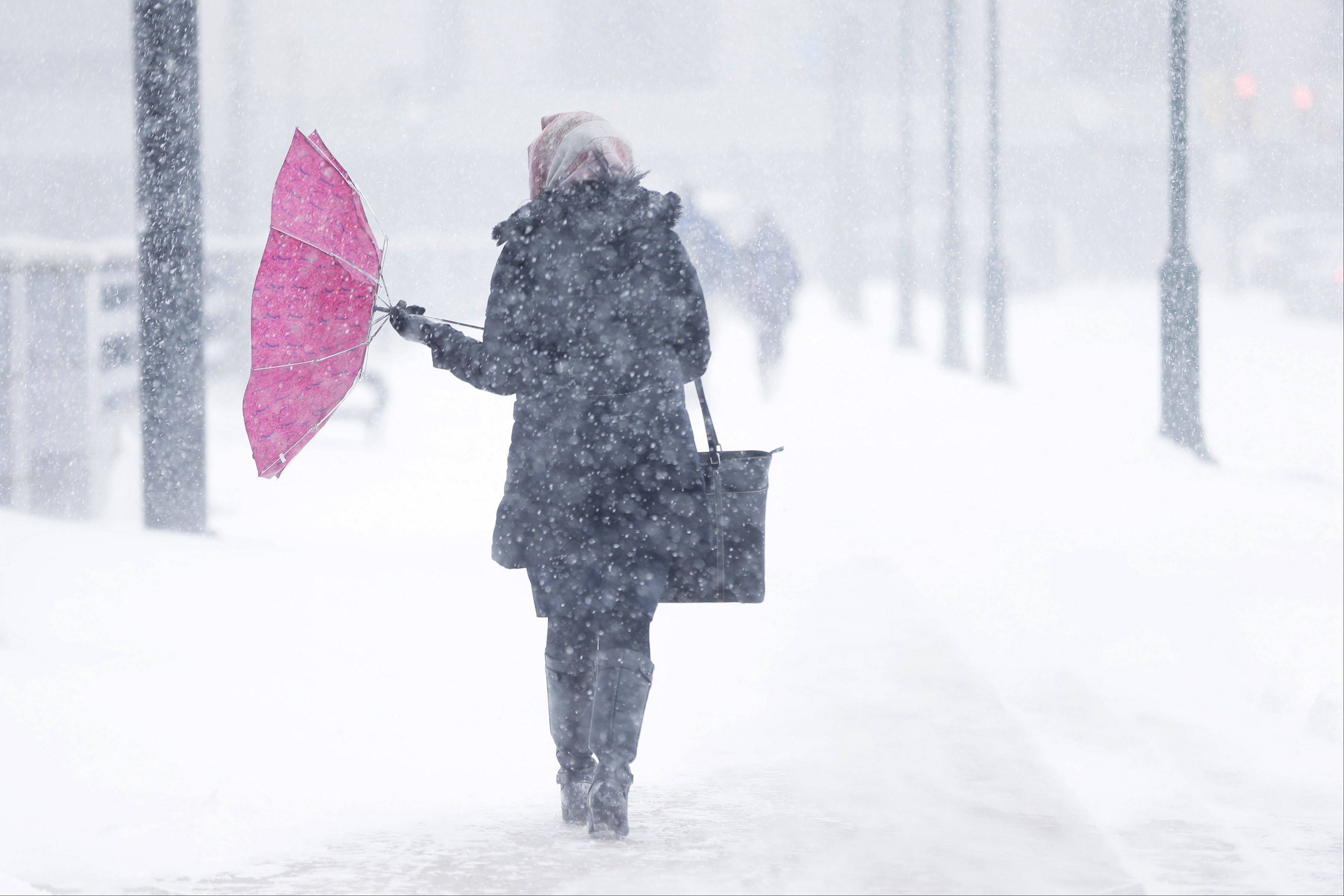 A pedestrian�s umbrellas is turned inside out during a winter snowstorm Tuesday in Philadelphia. A storm is sweeping across the Mid-Atlantic and New England. The National Weather Service said the storm could bring 8 to 12 inches of snow to Philadelphia and New York City, and more than a foot in Boston.